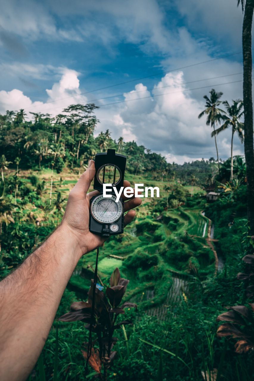 human hand, hand, human body part, plant, holding, photography themes, cloud - sky, sky, nature, real people, technology, tree, leisure activity, one person, camera - photographic equipment, activity, personal perspective, green color, lifestyles, day, outdoors, digital camera, finger, photographer