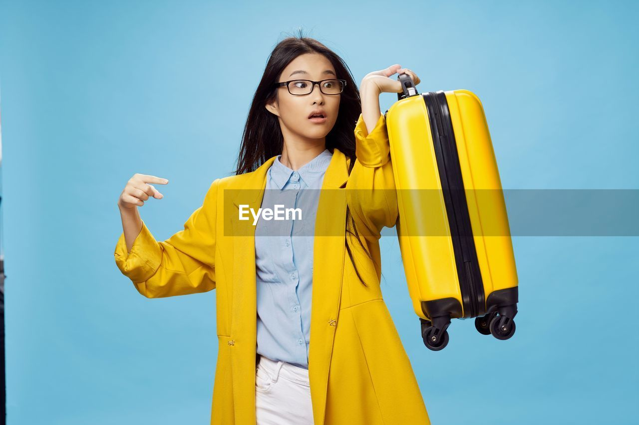 BEAUTIFUL YOUNG WOMAN STANDING AGAINST YELLOW BLUE SKY