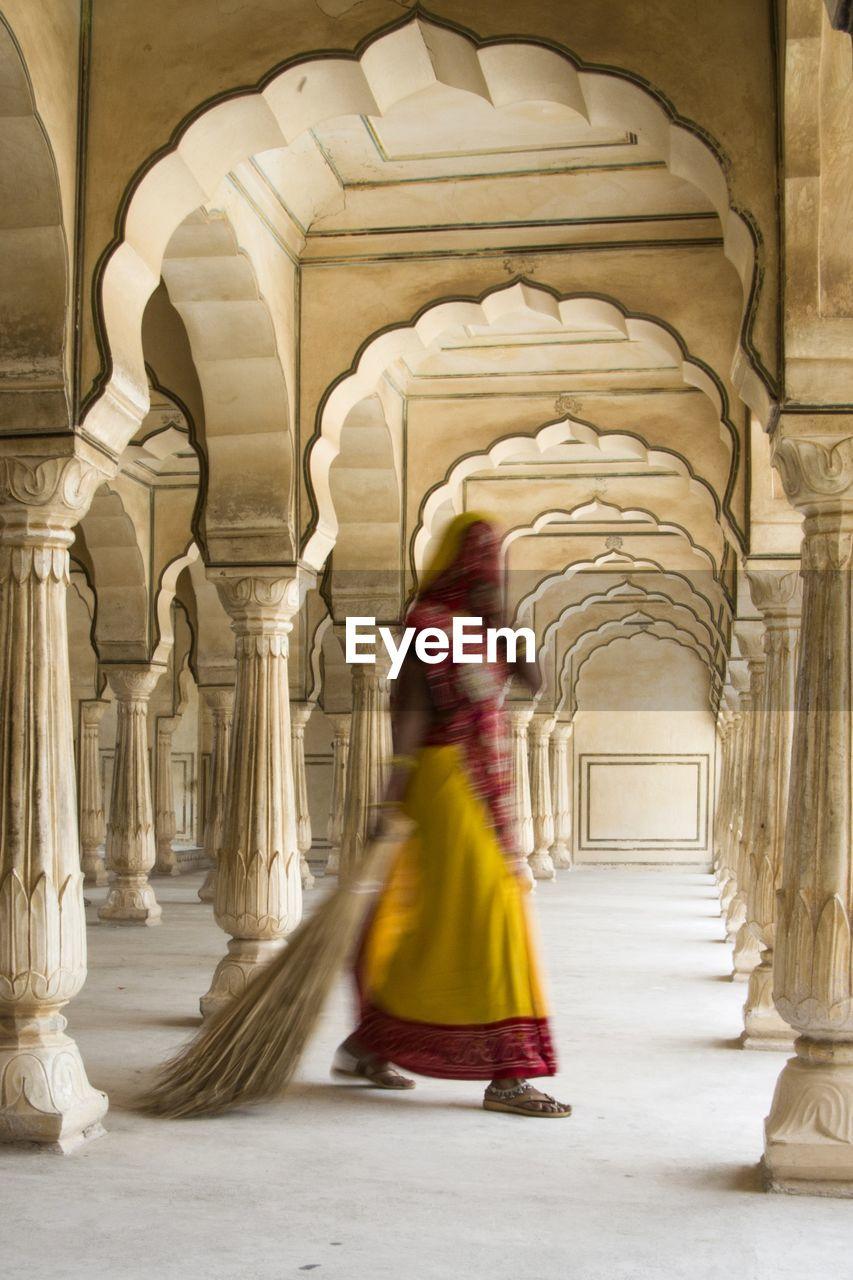 REAR VIEW OF WOMAN WALKING AT HISTORIC BUILDING