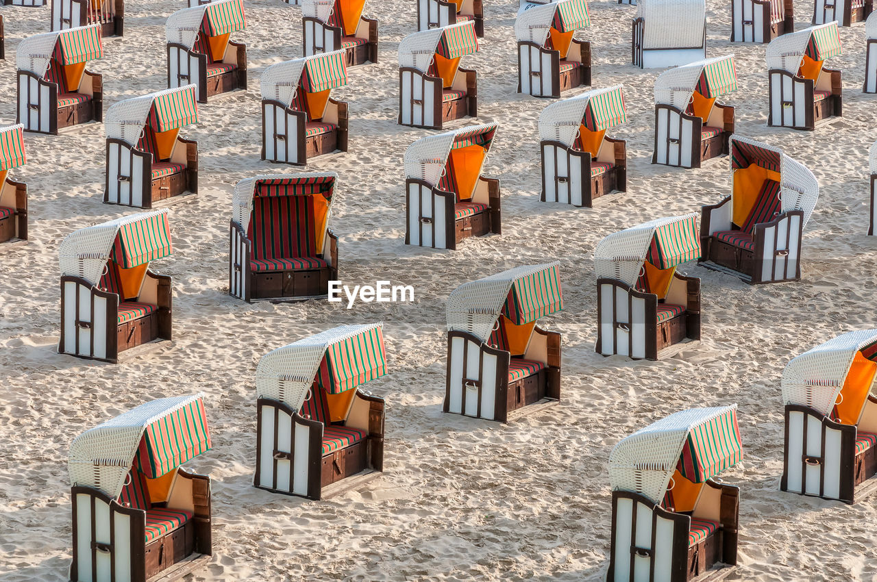 HIGH ANGLE VIEW OF CHAIRS ON BEACH AGAINST BUILDINGS