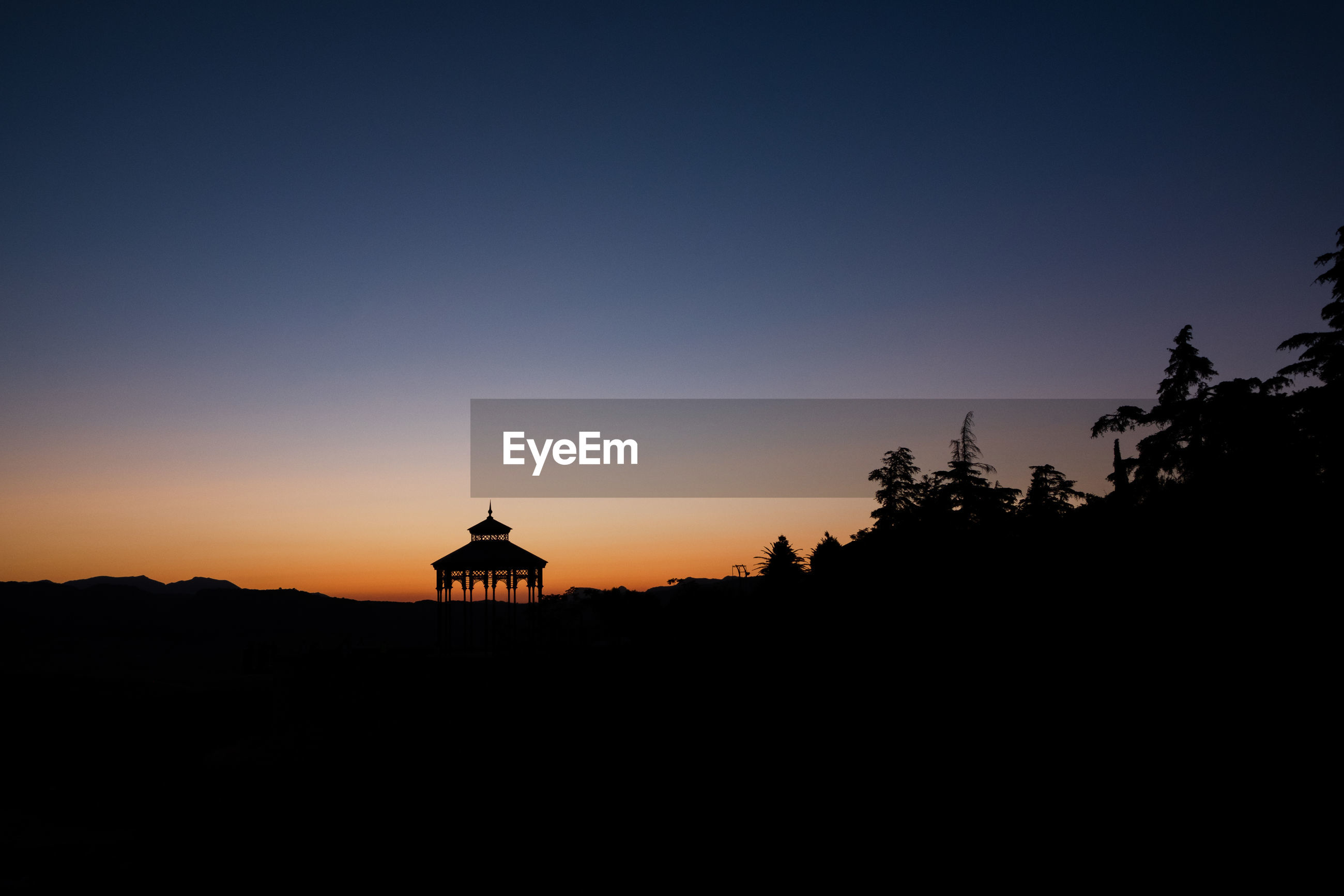 Silhouette of a building against clear sky at sunset