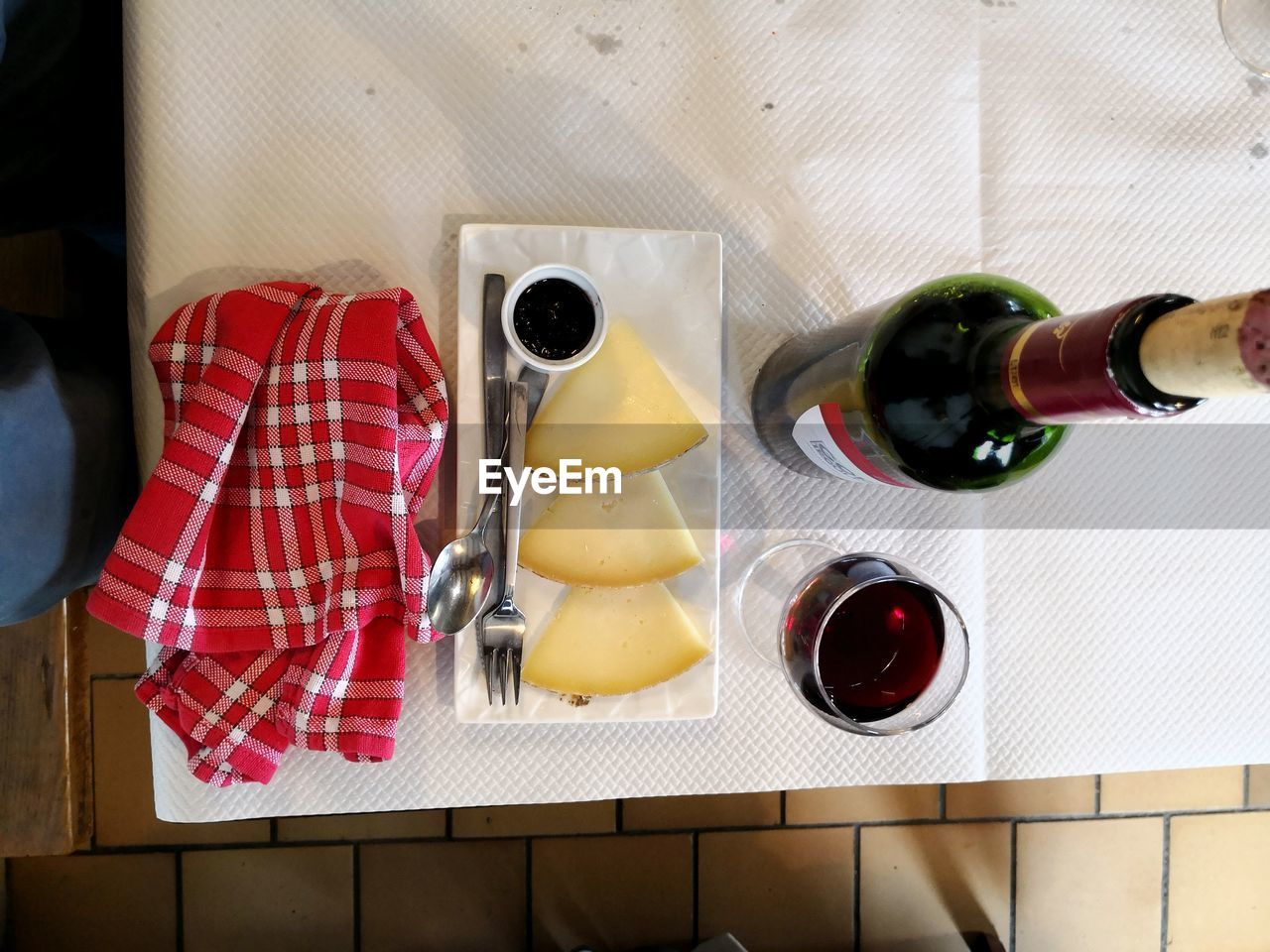 food and drink, food, indoors, bottle, alcohol, container, wine, refreshment, no people, freshness, drink, high angle view, wineglass, table, wine bottle, glass, still life, dairy product, checked pattern, cheese, red wine