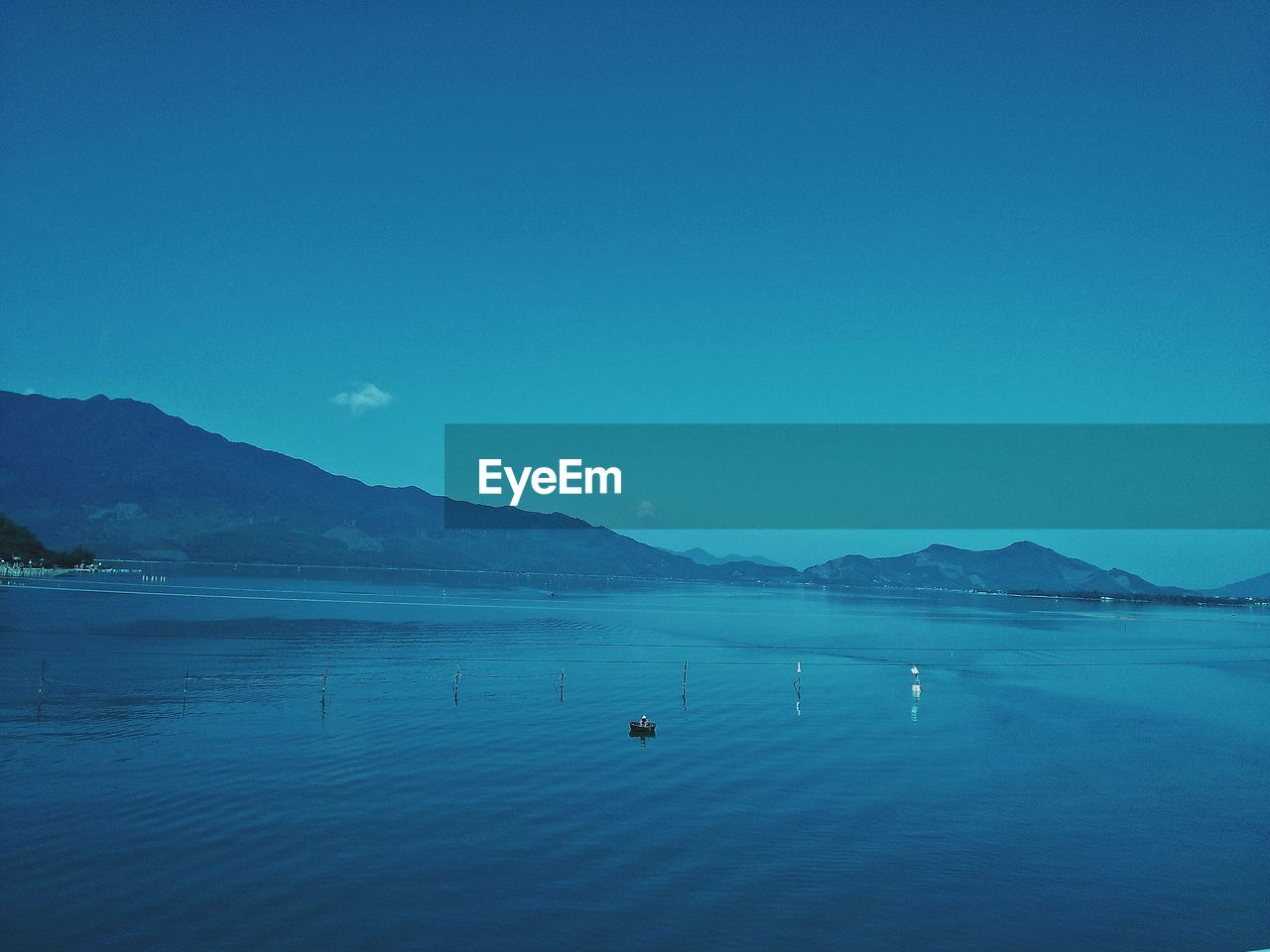 water, sky, mountain, scenics - nature, beauty in nature, blue, sea, waterfront, copy space, tranquil scene, tranquility, clear sky, nature, mountain range, nautical vessel, idyllic, non-urban scene, day, transportation, no people, outdoors