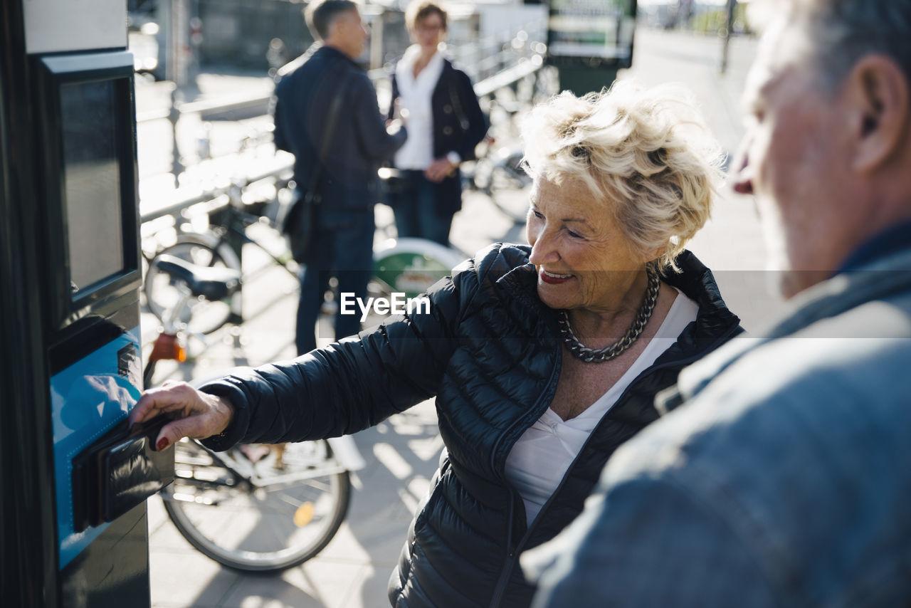 Senior woman operating bike vending machine by man on sidewalk in city