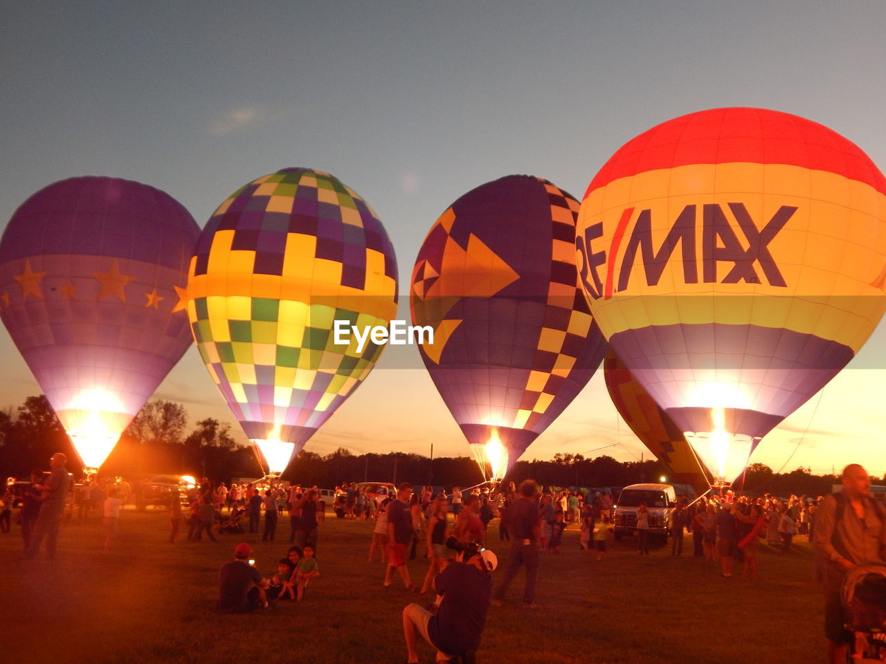 large group of people, celebration, illuminated, event, leisure activity, real people, ballooning festival, adventure, outdoors, enjoyment, traditional festival, crowd, fun, clear sky, night, hot air balloon, lifestyles, sky, men, women, people