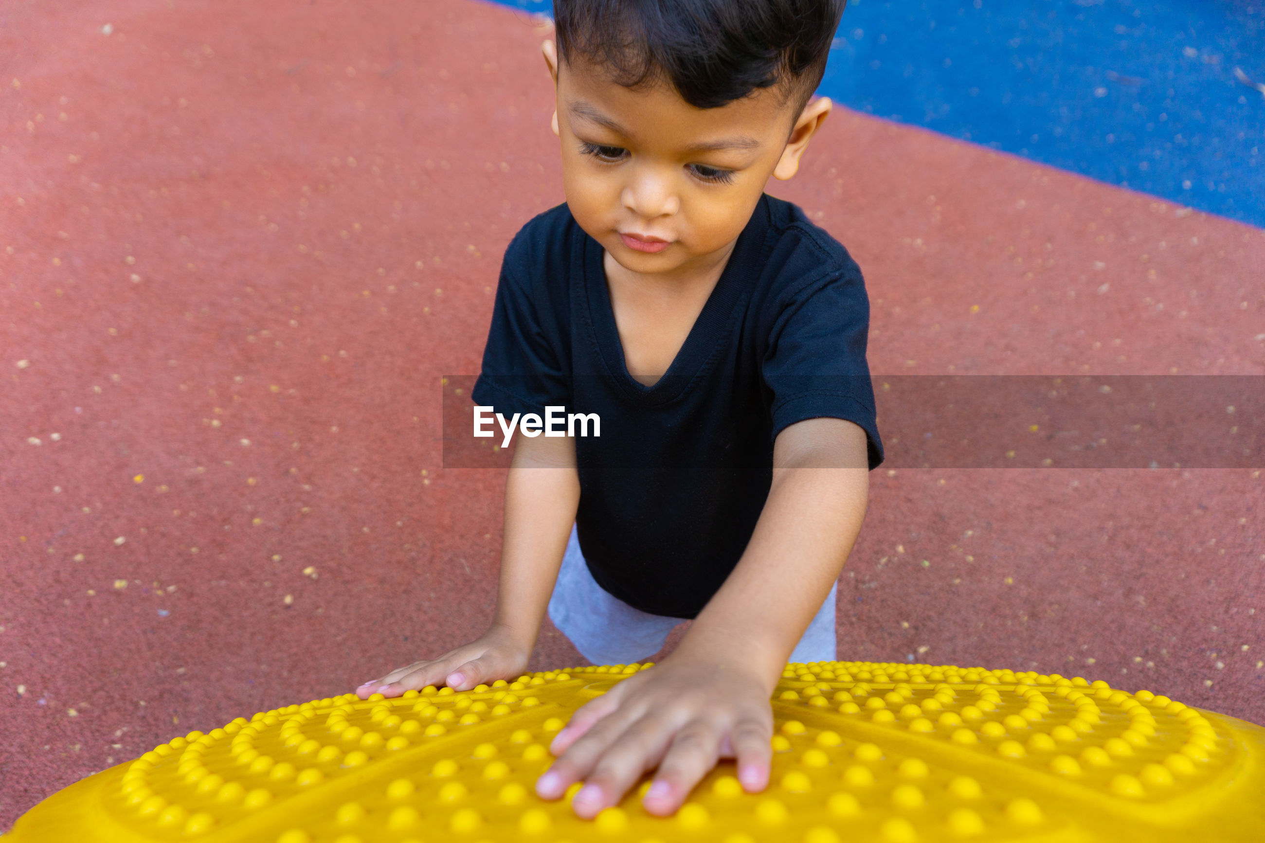 High angle view of boy playing with outdoor play equipment
