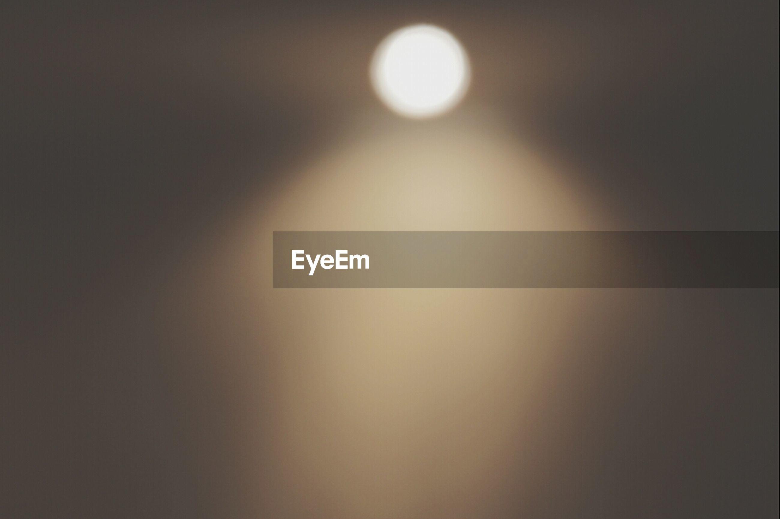 Defocused image of spotlight in dark room