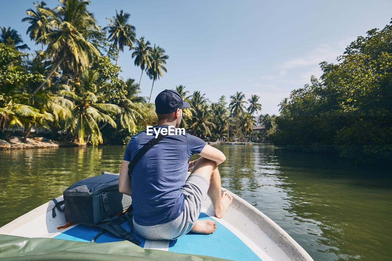 Rear view of man sitting on rowboat in lake at forest