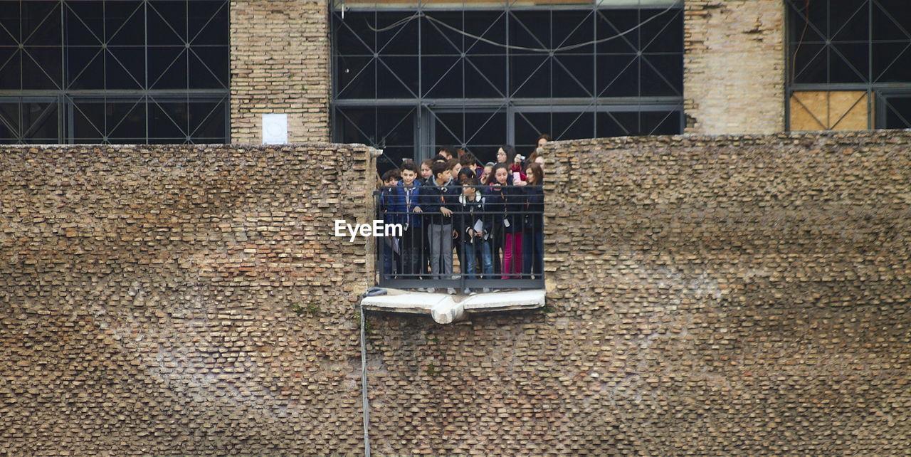 MEN STANDING ON COBBLESTONE
