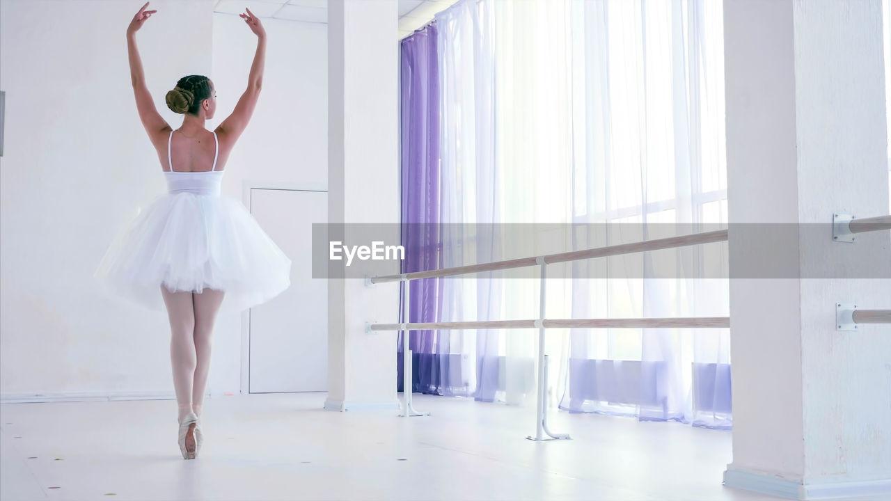 Rear view of ballerina dancing in studio