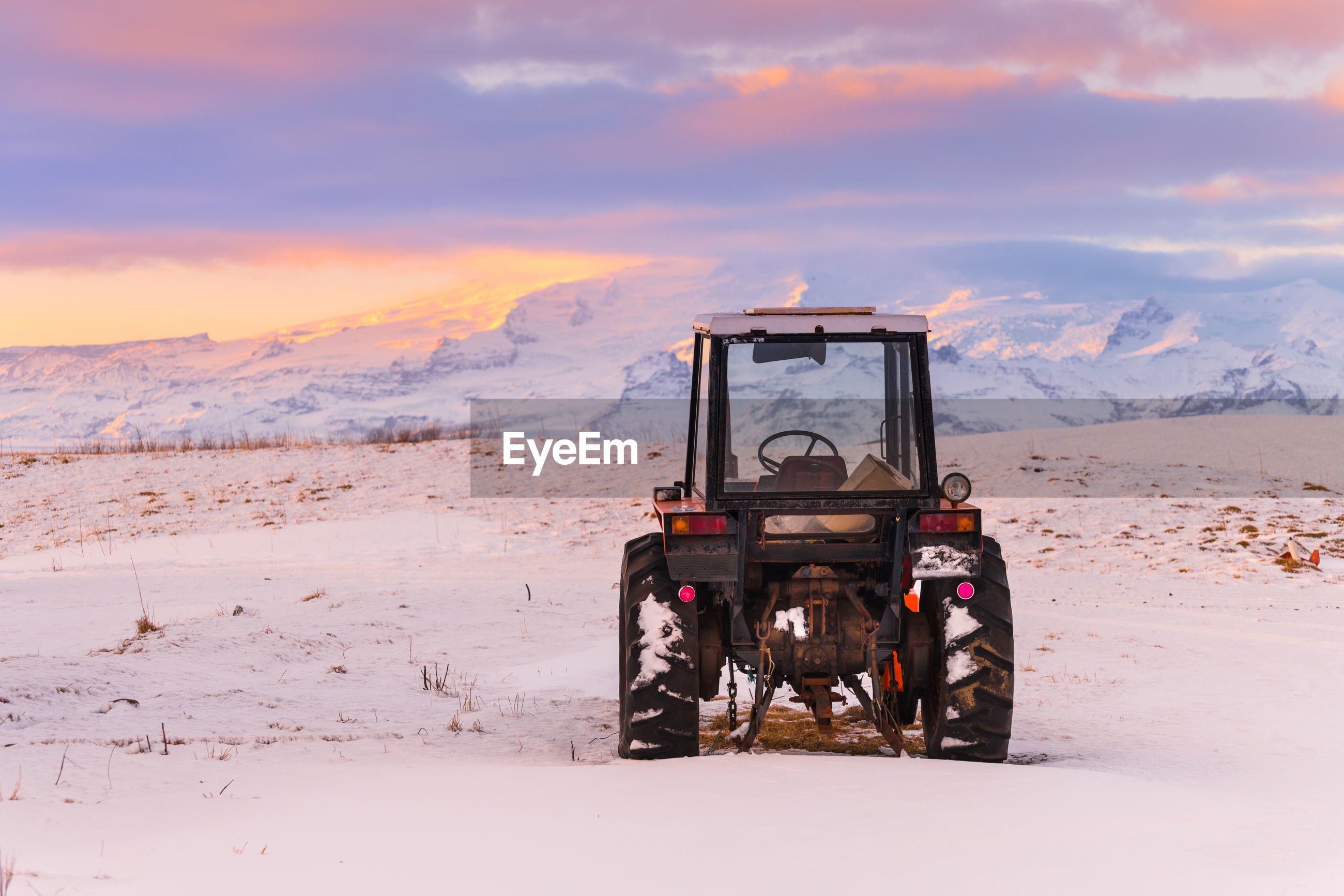 BUILT STRUCTURE ON FIELD AGAINST SNOWCAPPED MOUNTAINS DURING SUNSET