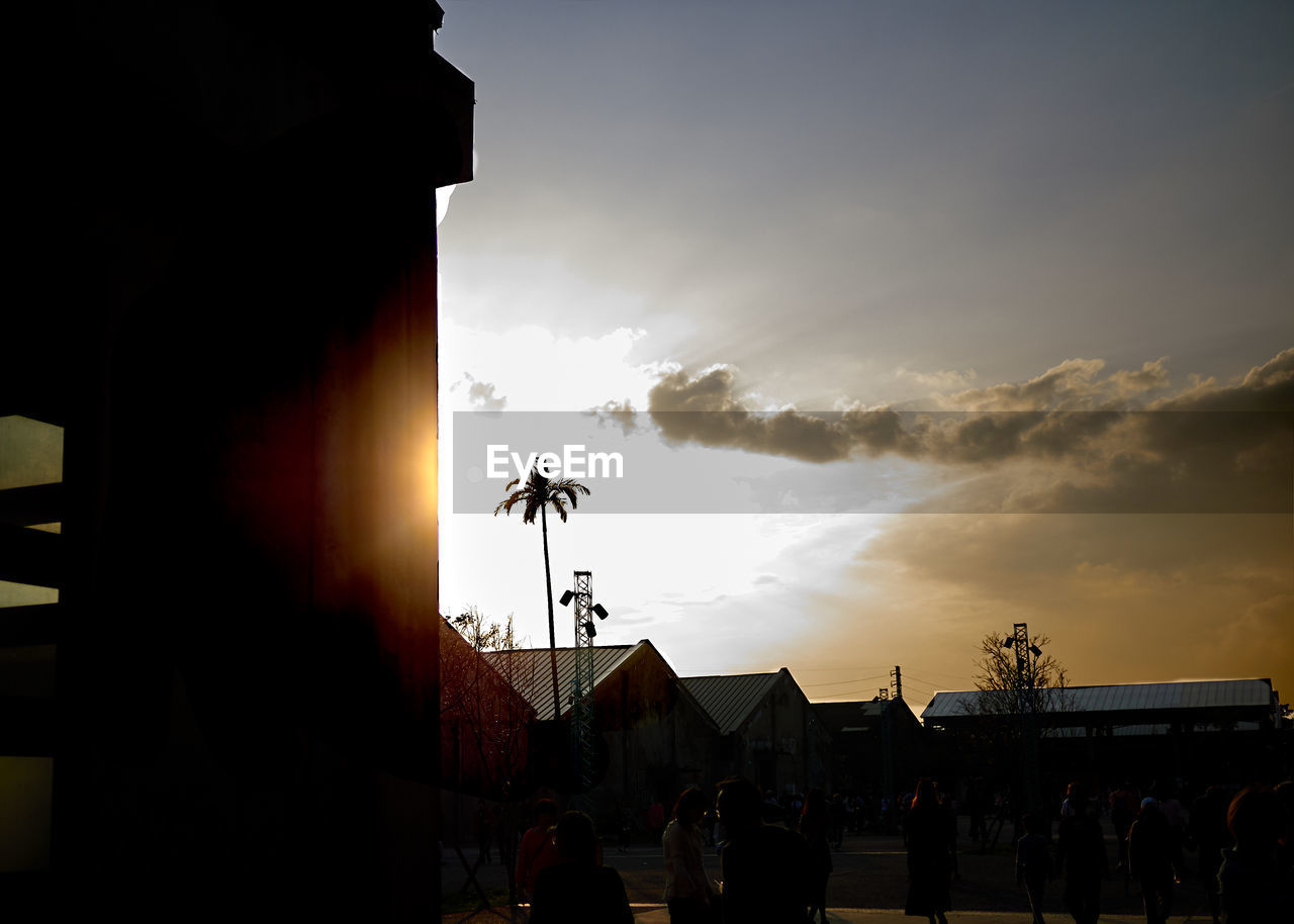 sky, cloud - sky, architecture, silhouette, built structure, sunset, real people, nature, building exterior, group of people, sunlight, outdoors, building, lifestyles, men, crowd, sun, people, orange color