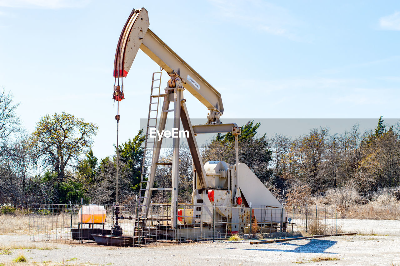 oil industry, oil pump, oil field, industry, fuel and power generation, oil well, no people, day, industrial equipment, outdoors, sky, drilling rig, tree, manufacturing equipment