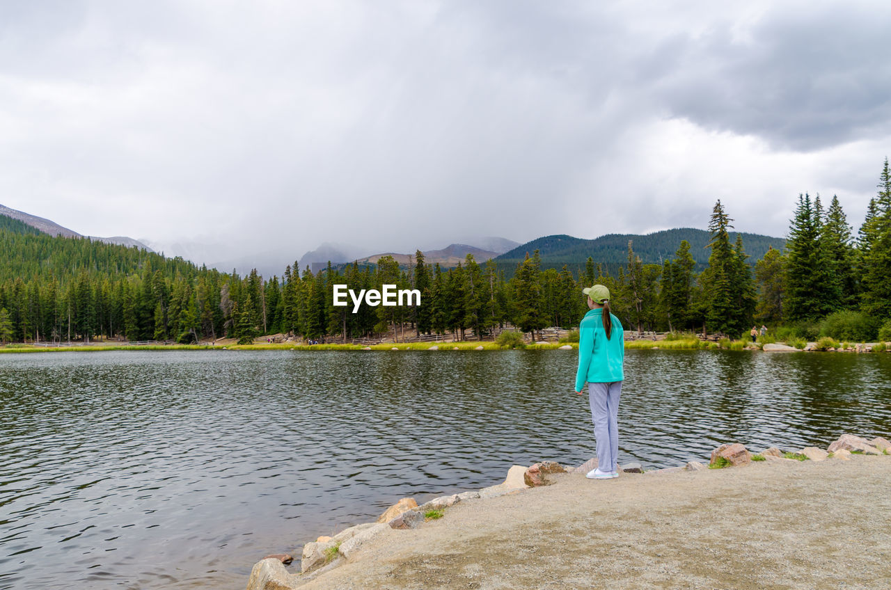 rear view, real people, full length, standing, nature, one person, mountain, leisure activity, sky, men, tree, scenics, lake, beauty in nature, casual clothing, day, cloud - sky, water, lifestyles, outdoors, young adult, adult, people