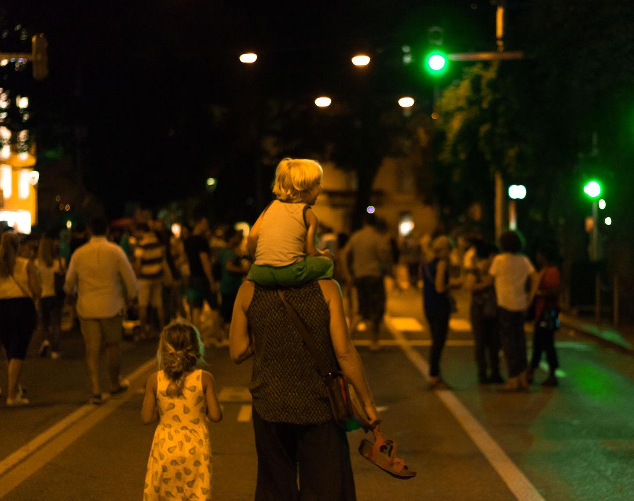 CROWD WALKING ON STREET AT NIGHT