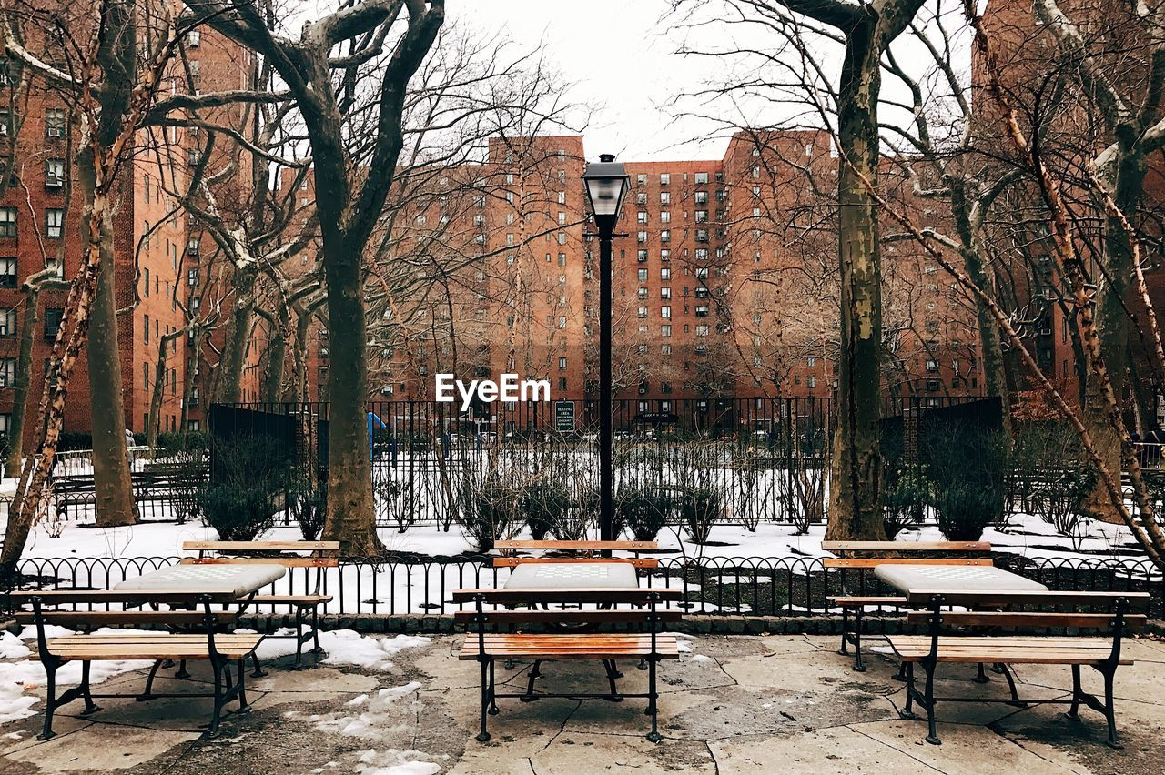 Benches and tables by walkway in city during winter