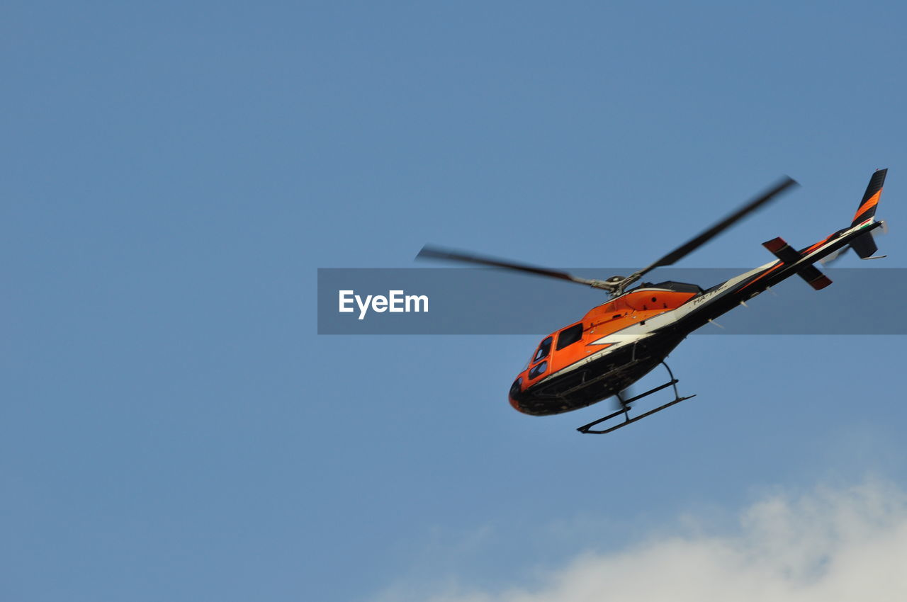Low angle view of helicopter against sky