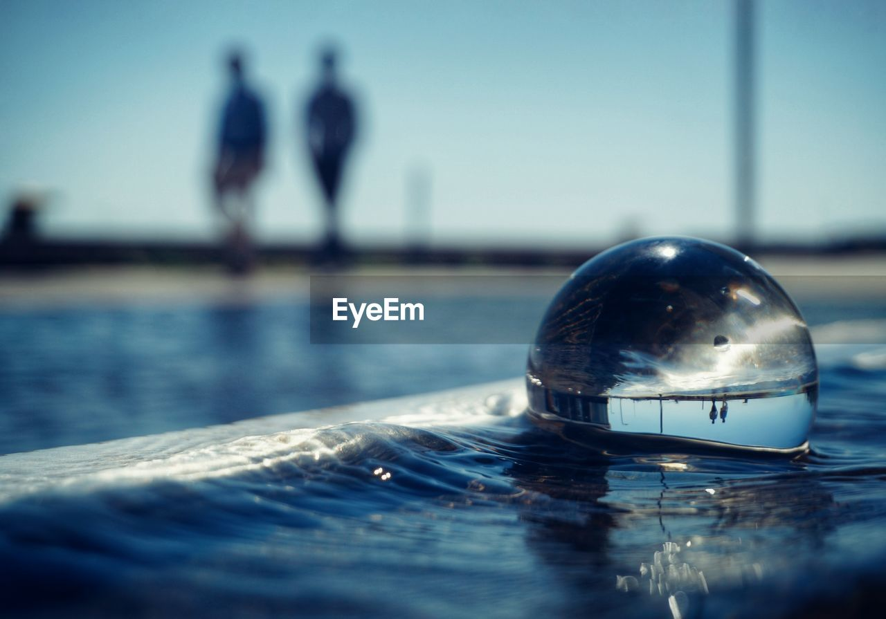 water, reflection, nature, sphere, sky, day, close-up, focus on foreground, selective focus, pool, swimming pool, waterfront, crystal ball, outdoors, sunlight, sea, ball, no people, clear sky, surface level