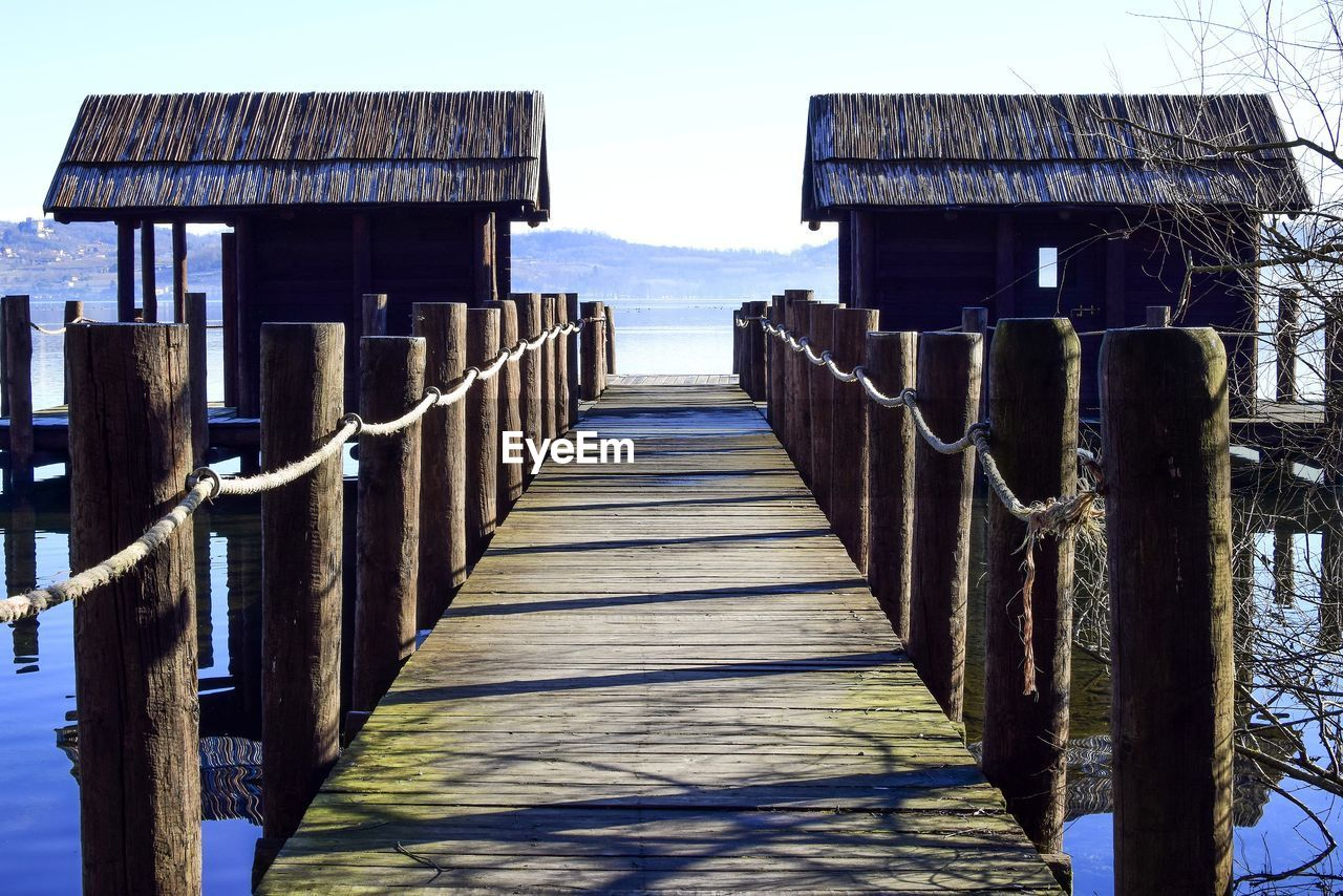 wood - material, built structure, sky, architecture, direction, water, nature, the way forward, day, sea, no people, post, wooden post, land, railing, pier, sunlight, outdoors, tranquility, wood, long, wood paneling