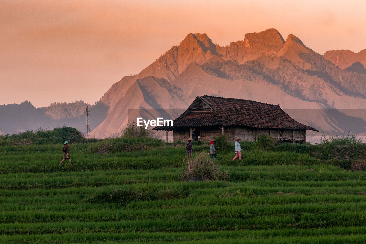 BUILT STRUCTURE ON FIELD AGAINST MOUNTAINS