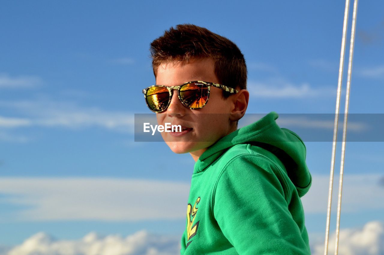 Low Angle View Of Boy Against Blue Sky