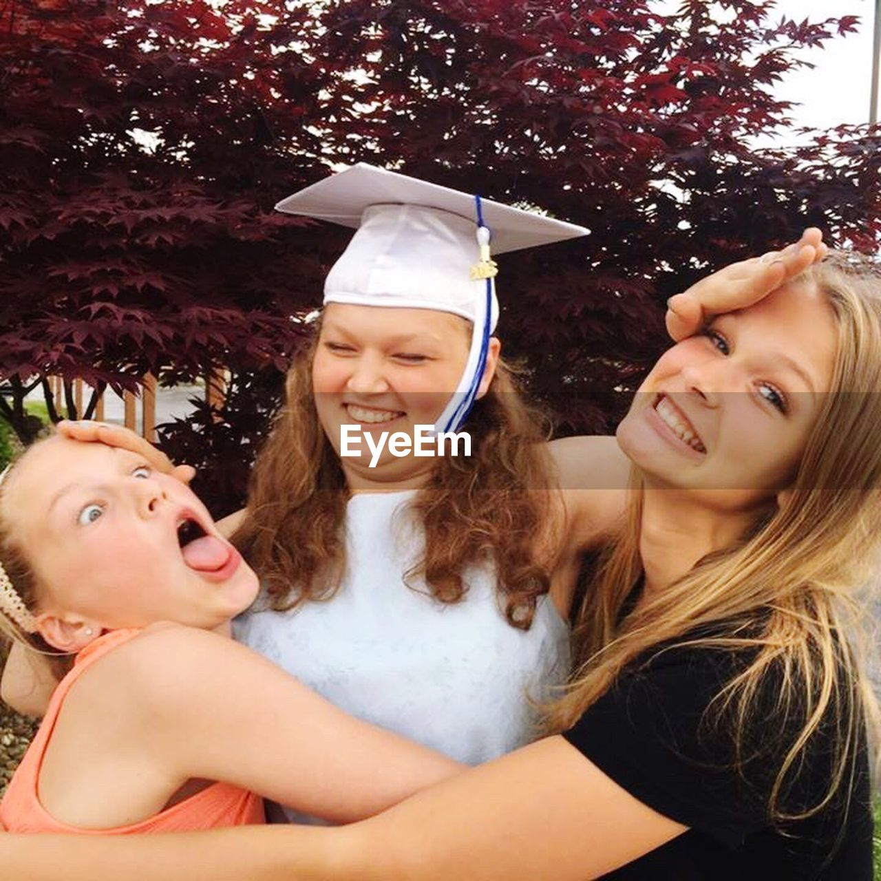 graduation, education, mortarboard, young adult, young women, university student, celebration, two people, togetherness, happiness, university, smiling, looking at camera, life events, cheerful, real people, friendship, day, portrait, outdoors, tree, blond hair, close-up, adult, people, adults only