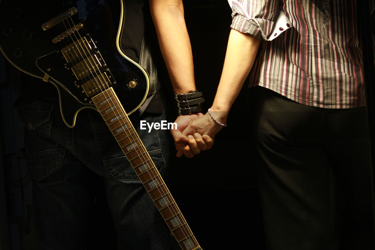 Midsection Of Man With Guitar Holding Hand Of Woman Over Black Background