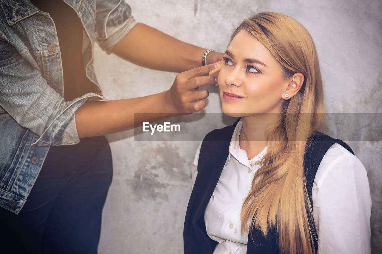 Midsection Of Woman Doing Make-Up For Customer