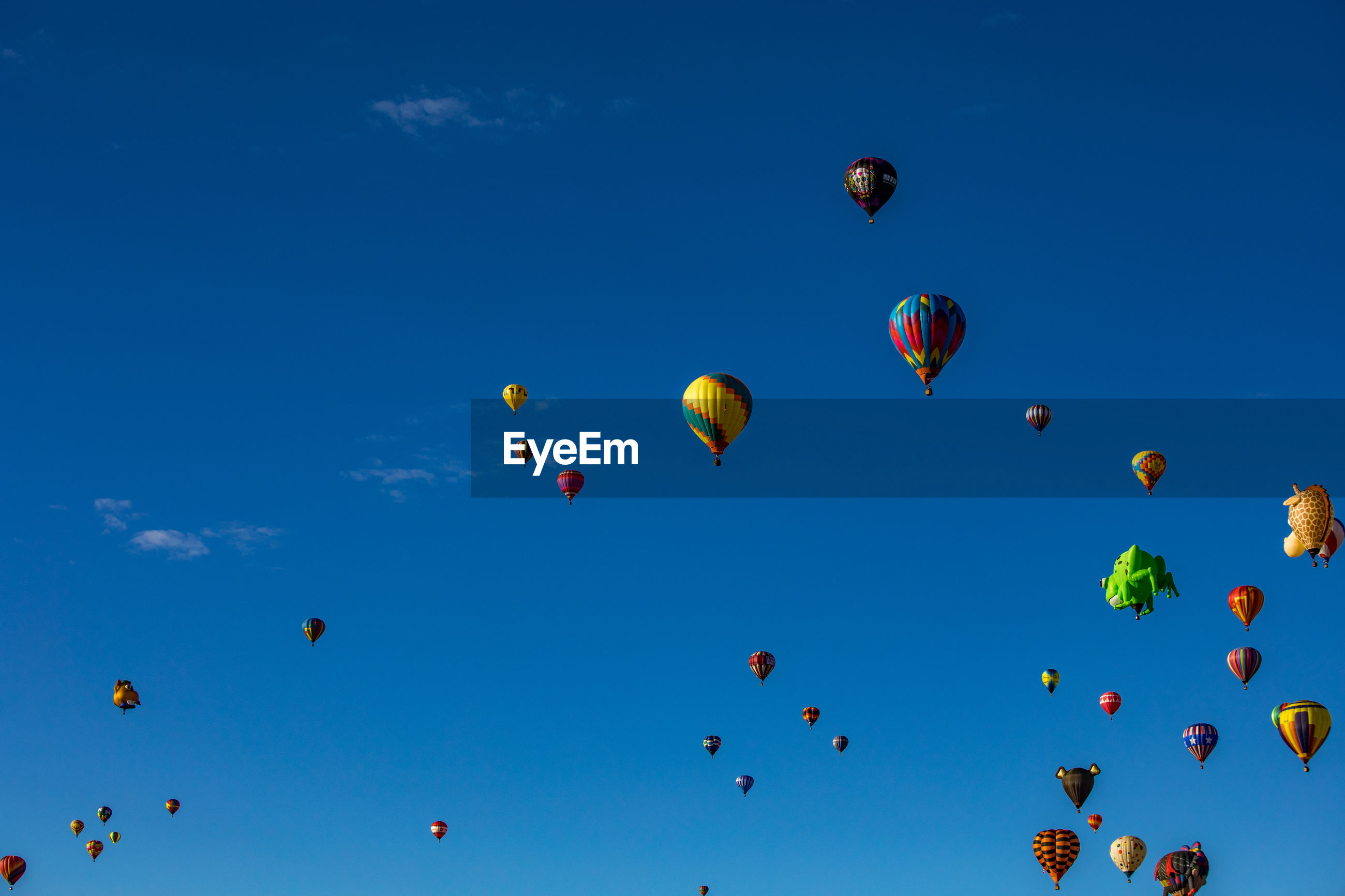 Low angle view of hot air balloons flying against blue sky