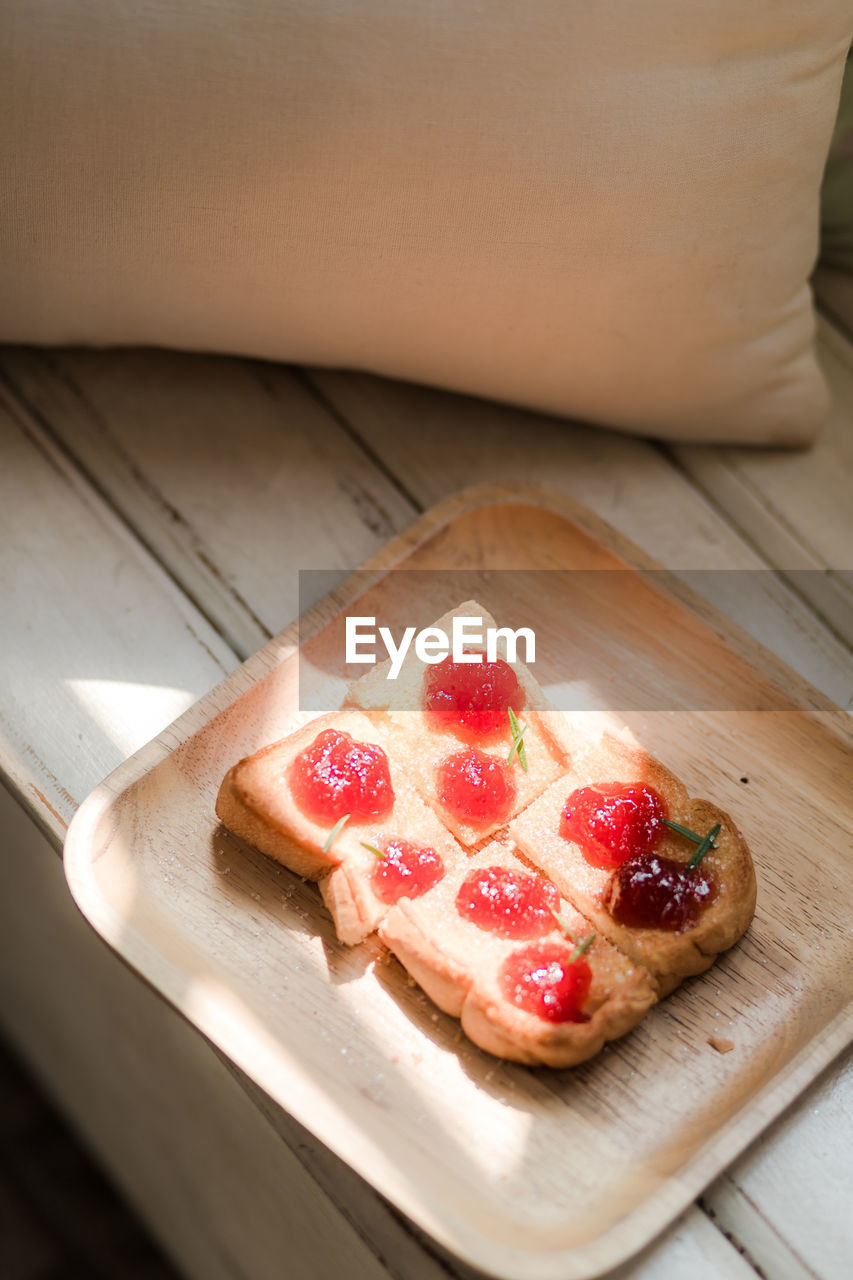 food, food and drink, freshness, indoors, table, fruit, still life, wood - material, high angle view, sweet food, red, no people, cutting board, sweet, healthy eating, close-up, berry fruit, dessert, slice, indulgence, temptation, snack