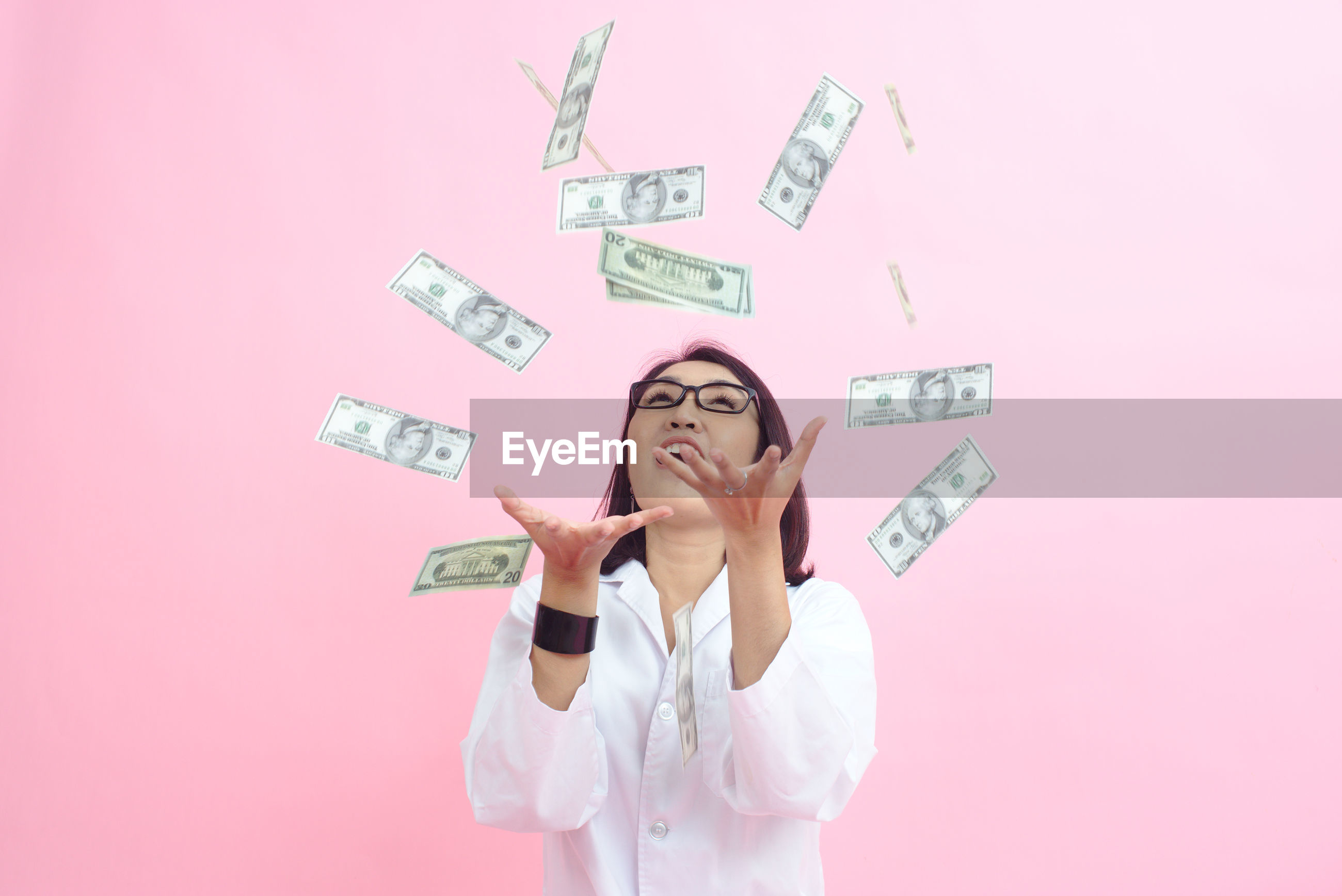 Woman trying to hold flying money against pink background