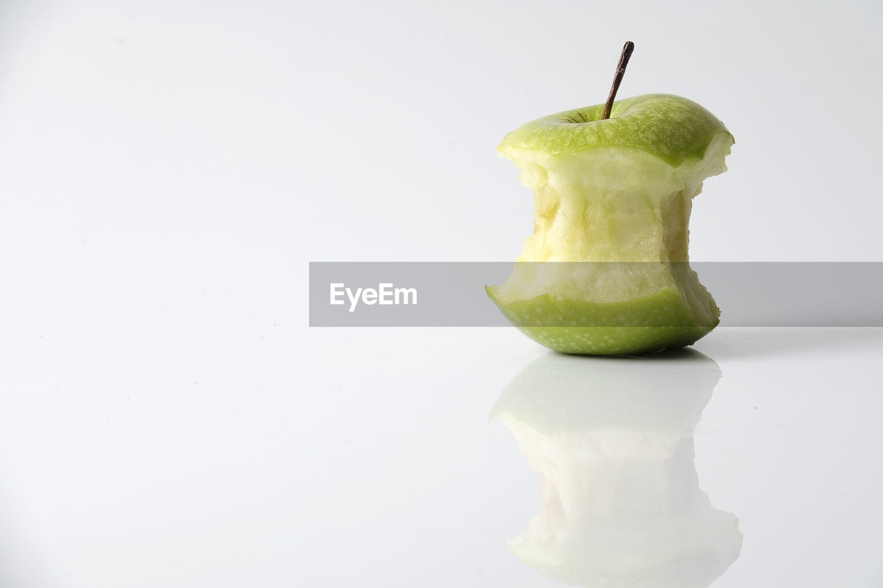 Close-up on eaten granny smith apple against white background