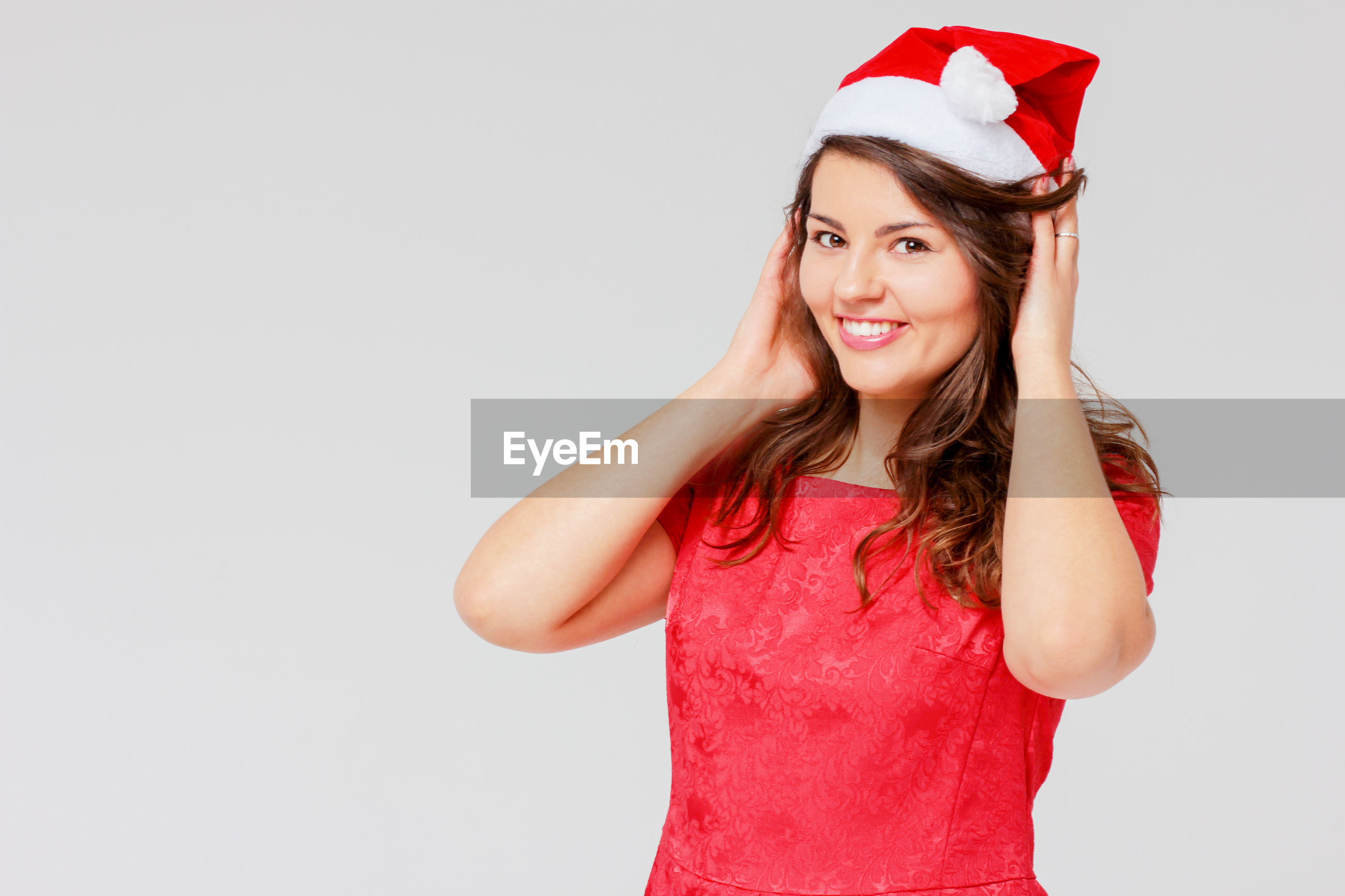 Portrait of happy young woman wearing santa hat while standing against gray background