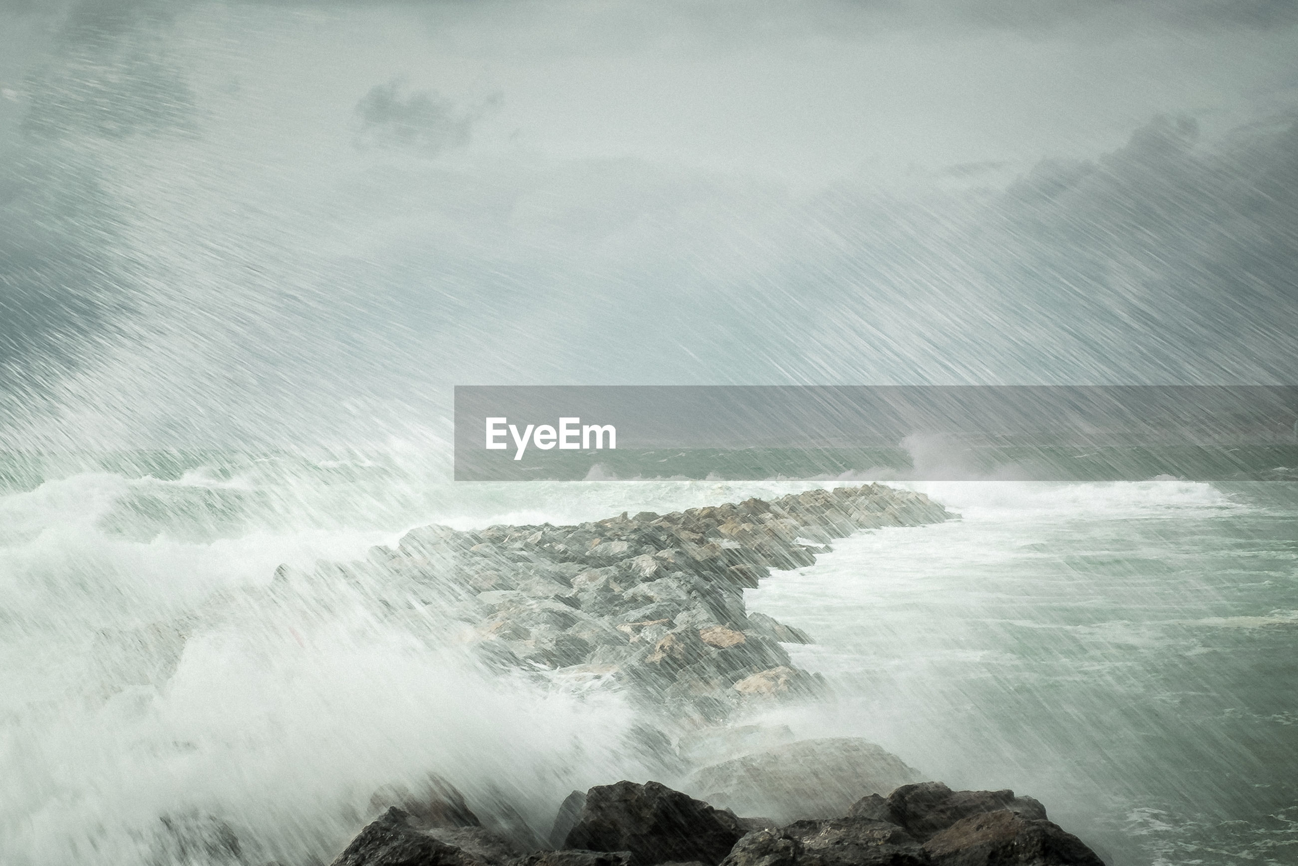 SCENIC VIEW OF WAVES BREAKING ON ROCKS