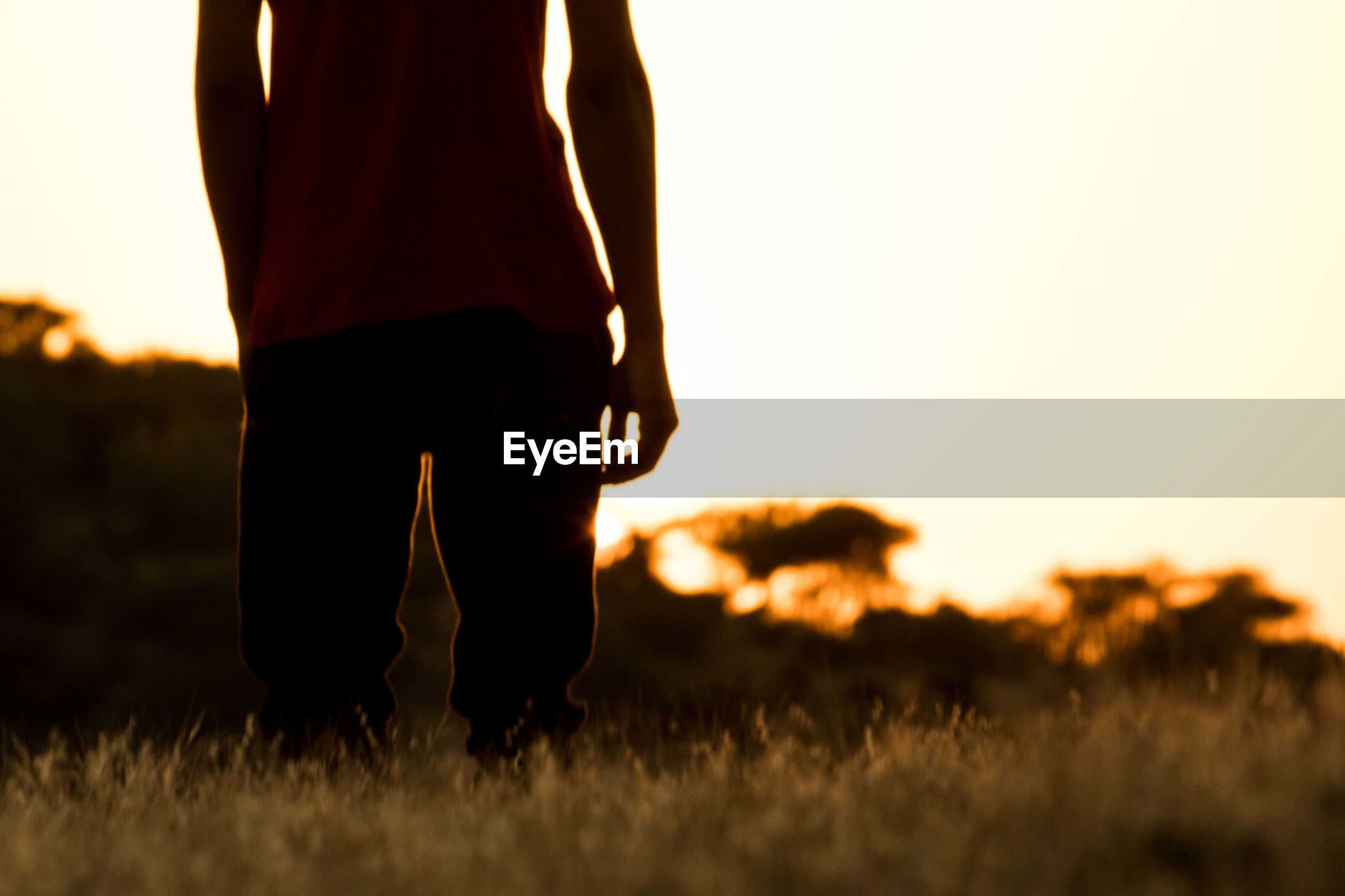 Midsection of man standing on field against sky during sunset