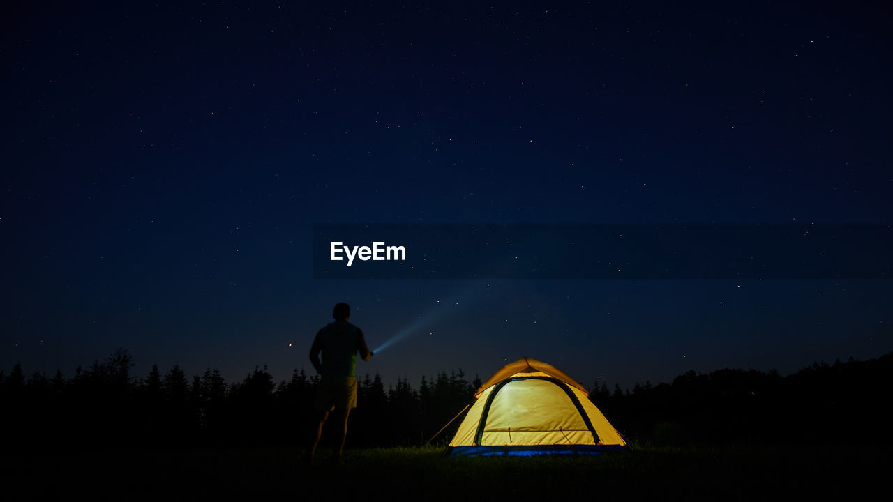 Rear View Of Man Flashing Light In Sky While Standing By Tent At Night