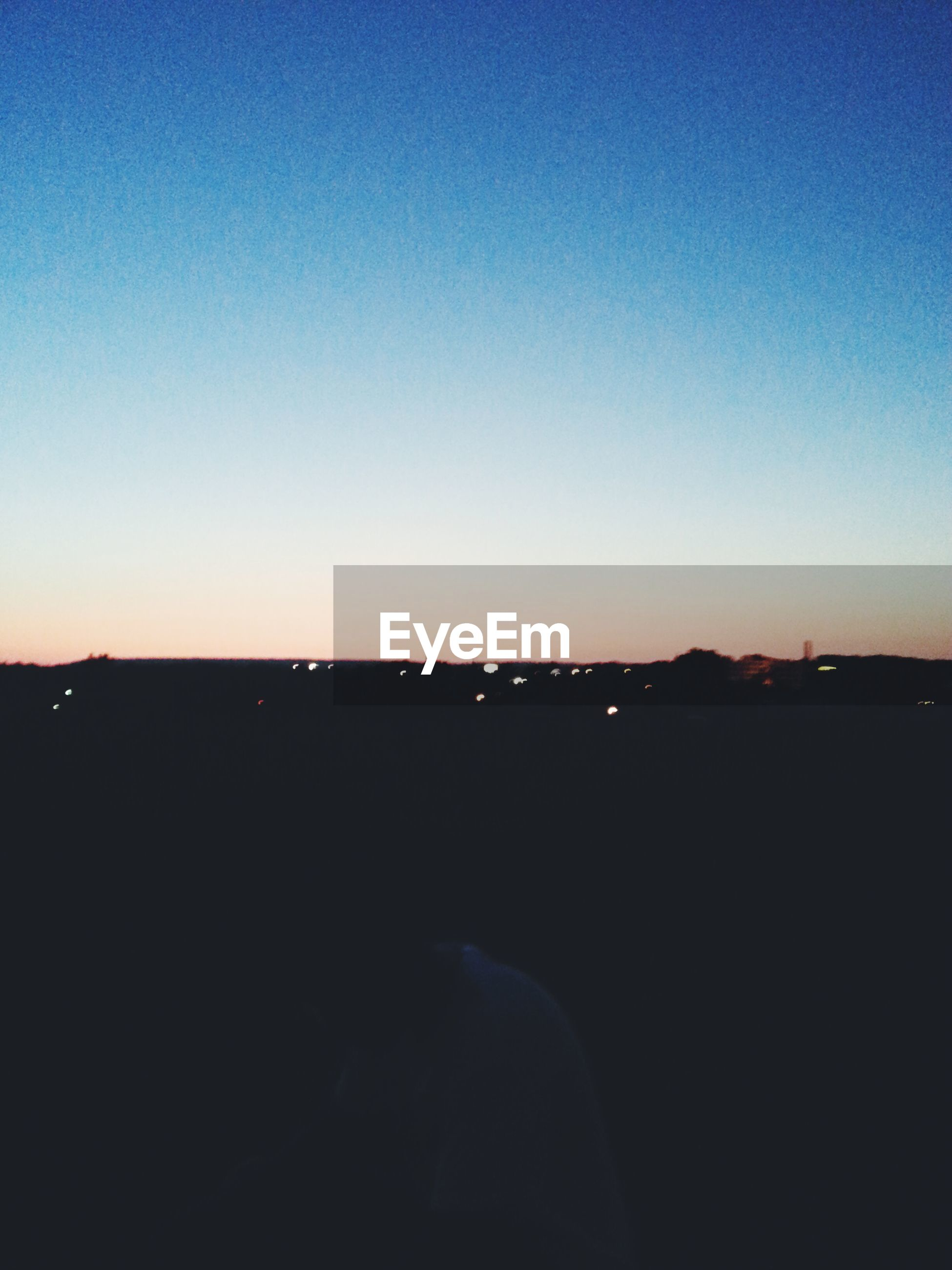 copy space, clear sky, sunset, silhouette, blue, dusk, dark, scenics, landscape, beauty in nature, tranquil scene, tranquility, orange color, nature, sky, outdoors, illuminated, city, building exterior, no people