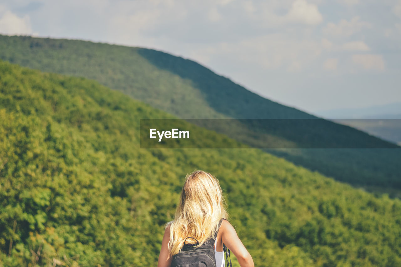 Rear view of young woman with backpack looking at mountains against sky