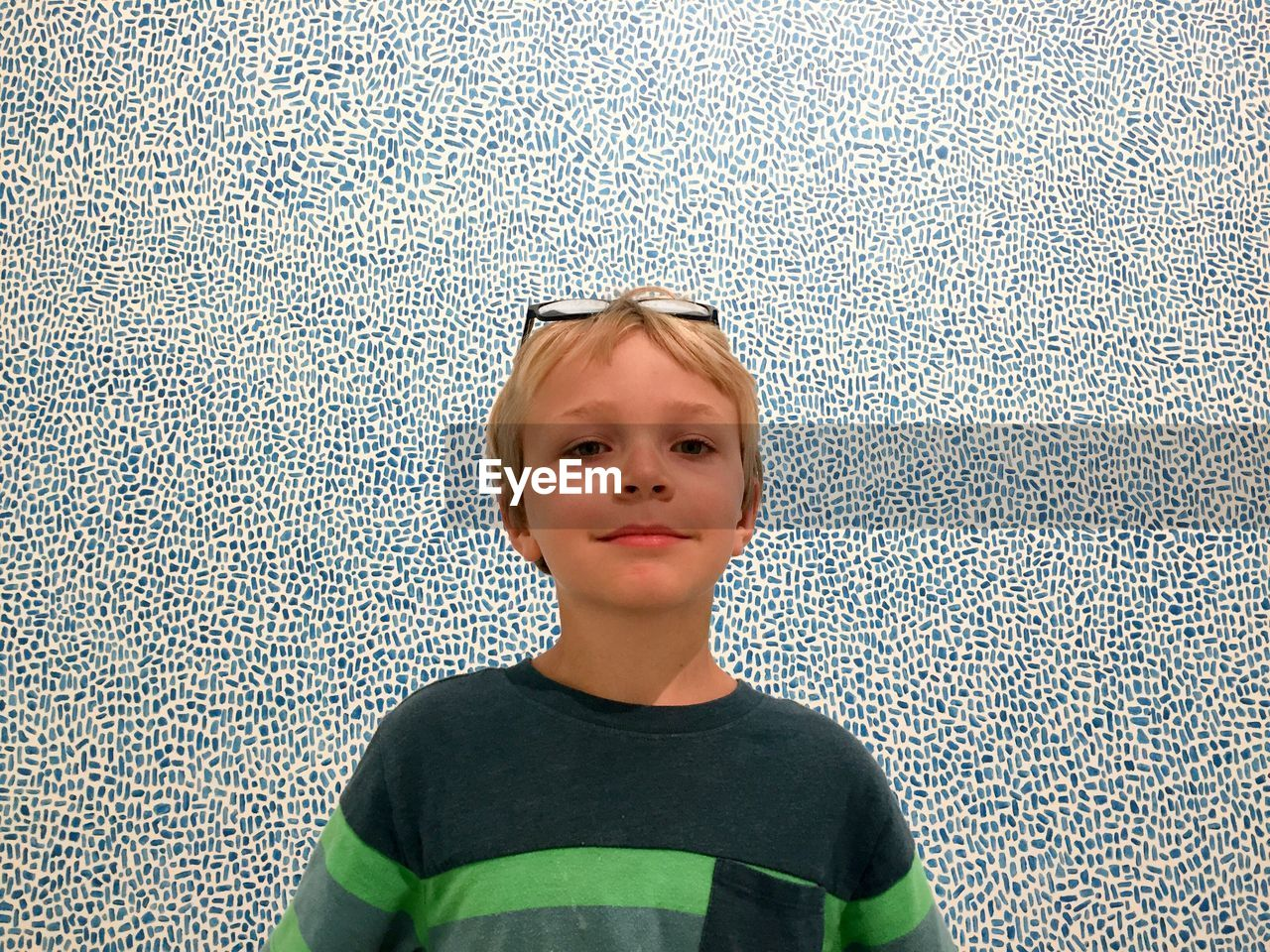 Portrait of smiling boy standing against patterned wall