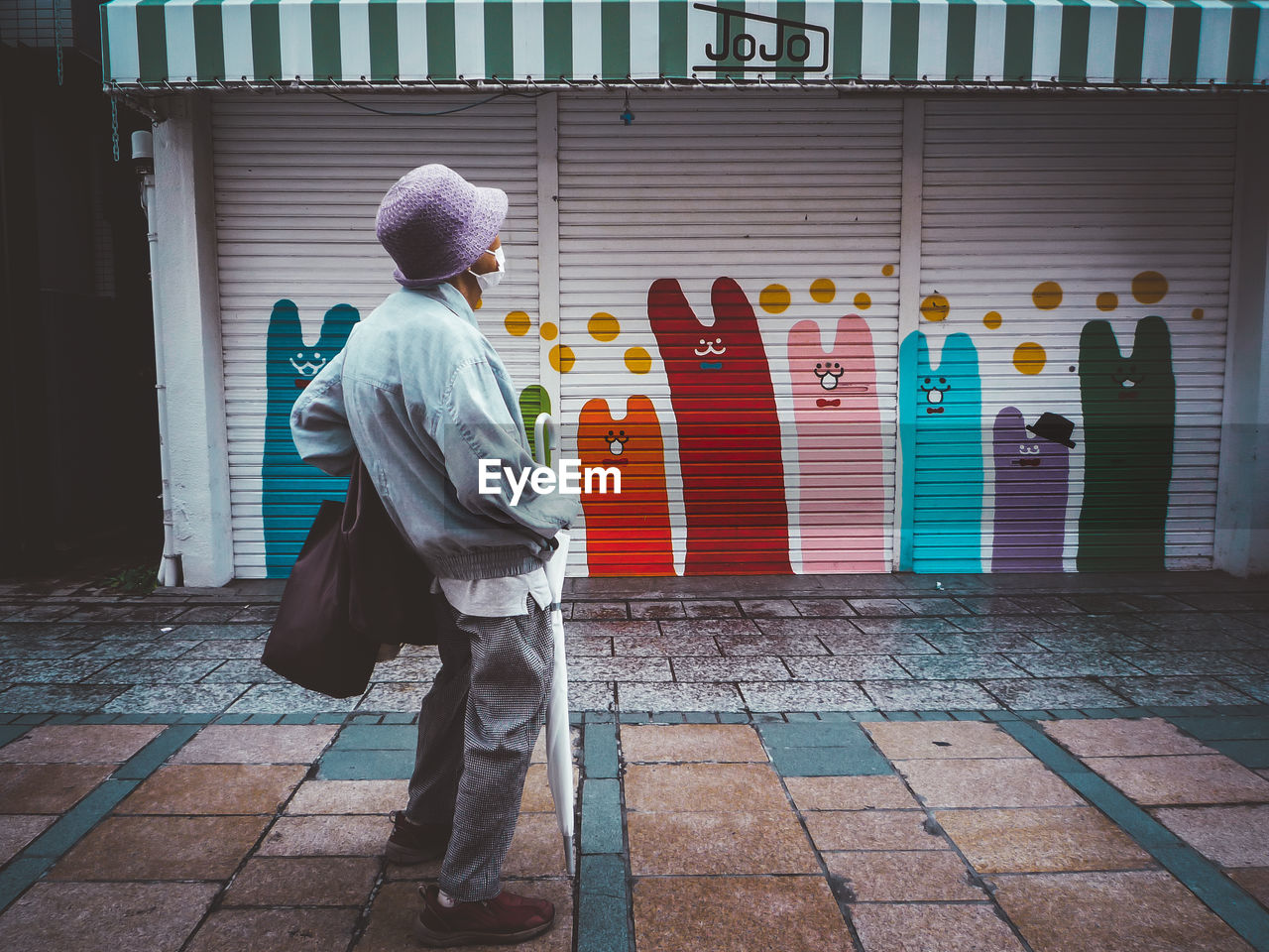 real people, architecture, built structure, full length, one person, building exterior, multi colored, rear view, walking, traditional clothing, day, lifestyles, creativity, building, religion, footpath, human representation, standing, representation