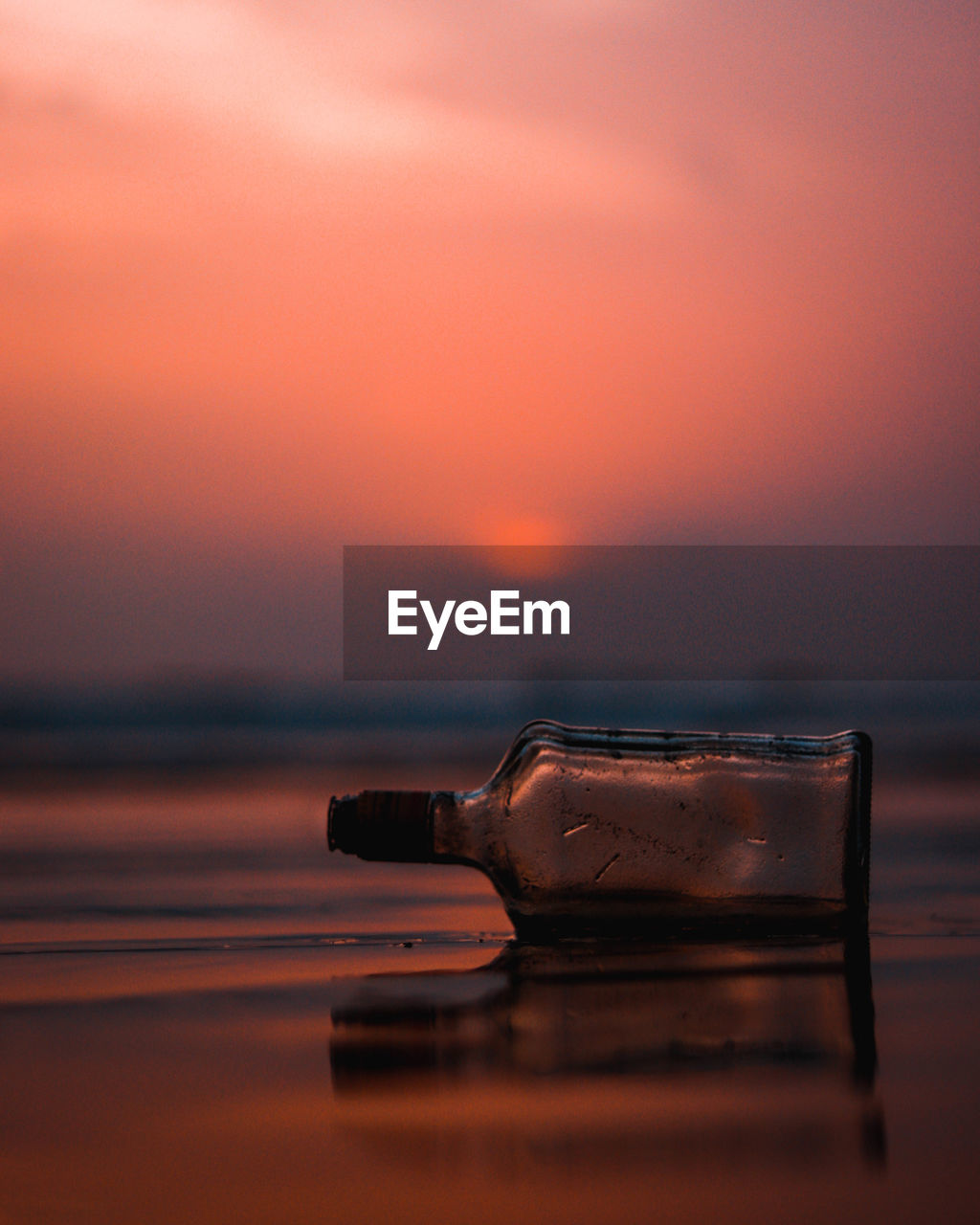 Close-up of empty glass bottle at beach during sunset