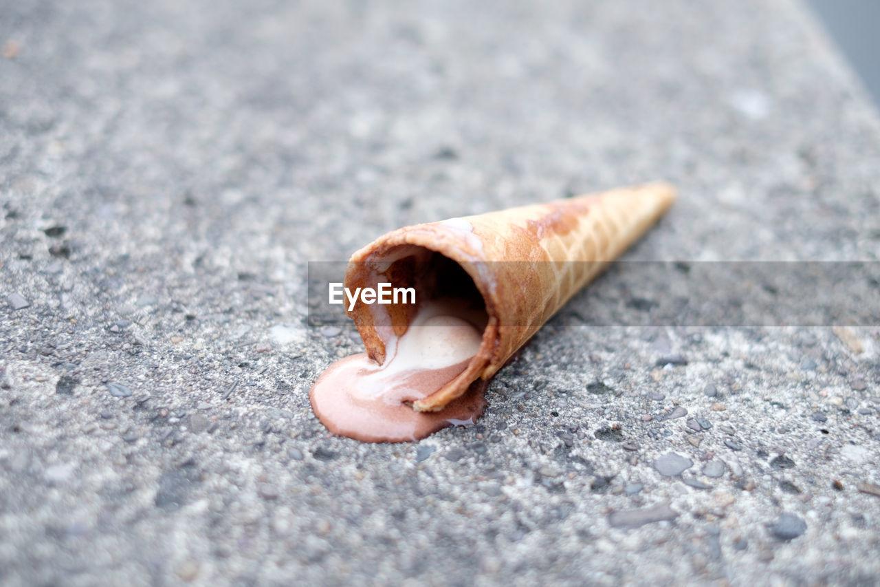 Close-Up Of Fallen Ice Cream Cone On Street