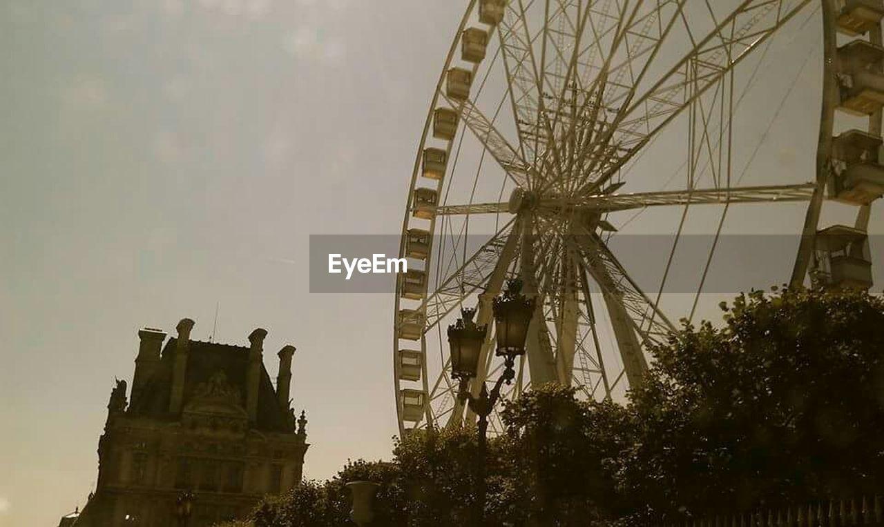 amusement park, low angle view, arts culture and entertainment, built structure, tree, amusement park ride, outdoors, sky, no people, day, ferris wheel, architecture, nature