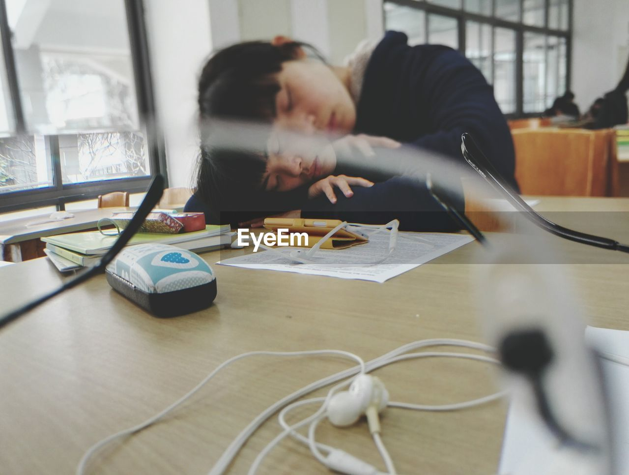 Young Woman Sleeping On Library Desk