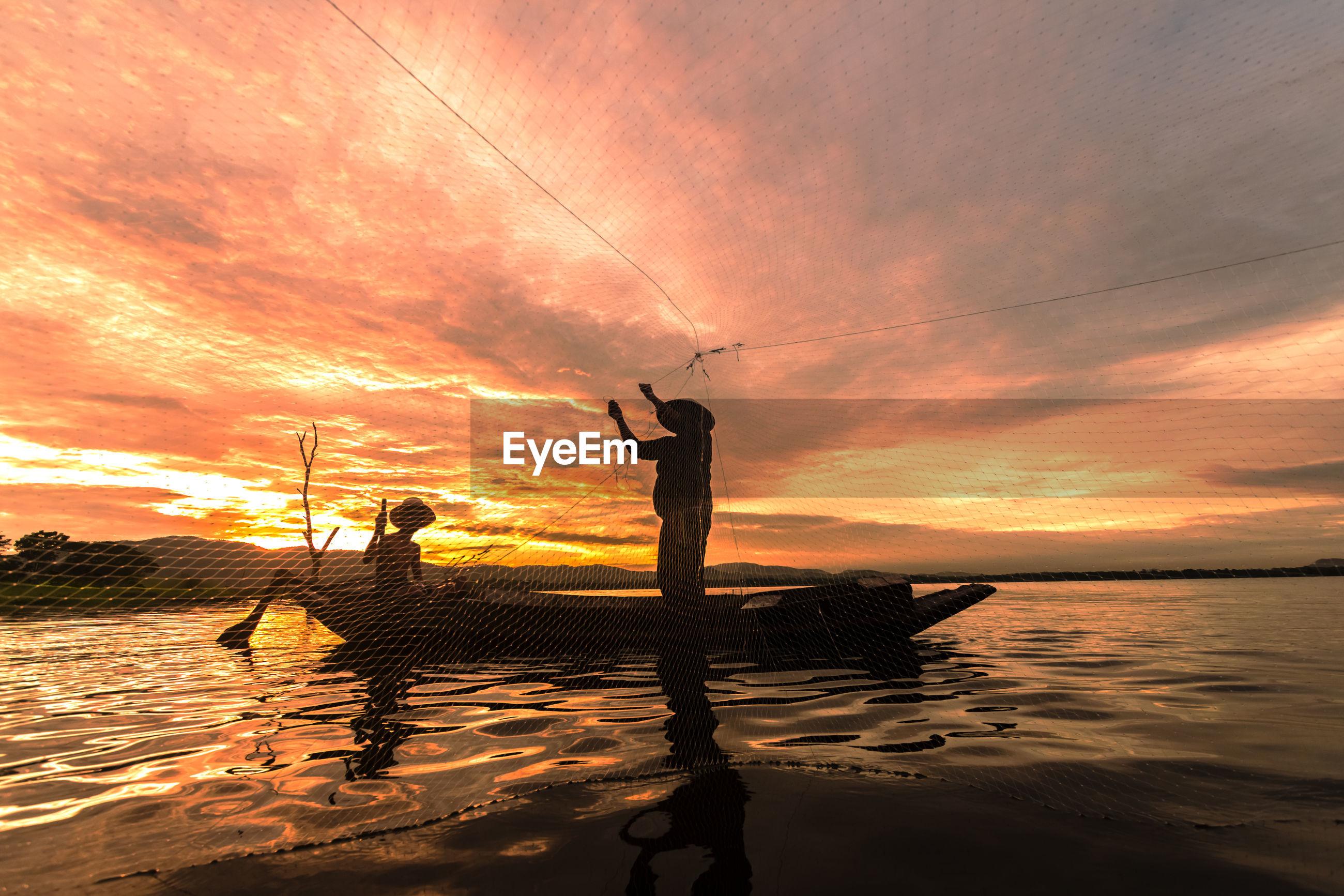 Silhouette fishermen fishing in sea against orange cloudy sky