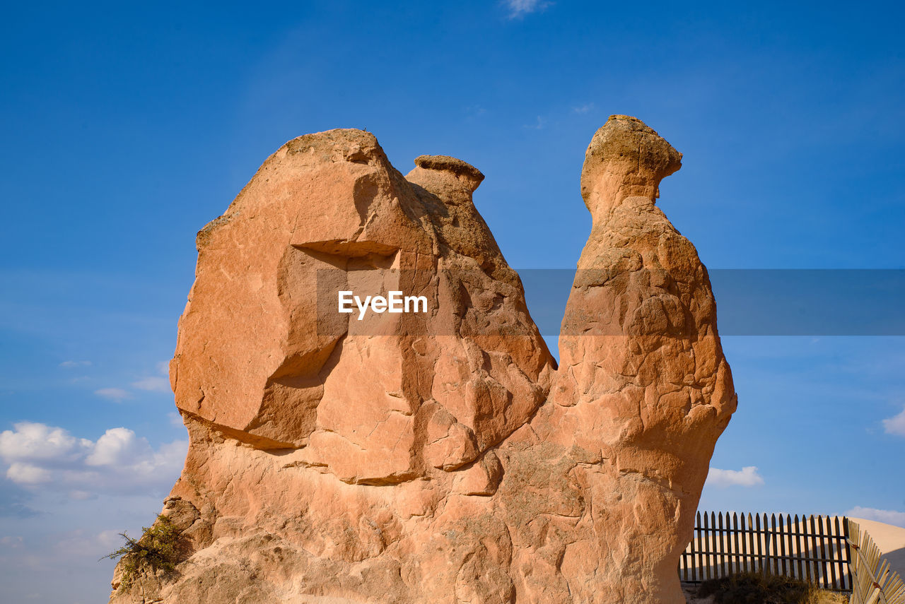 LOW ANGLE VIEW OF ROCK FORMATIONS AGAINST BLUE SKY