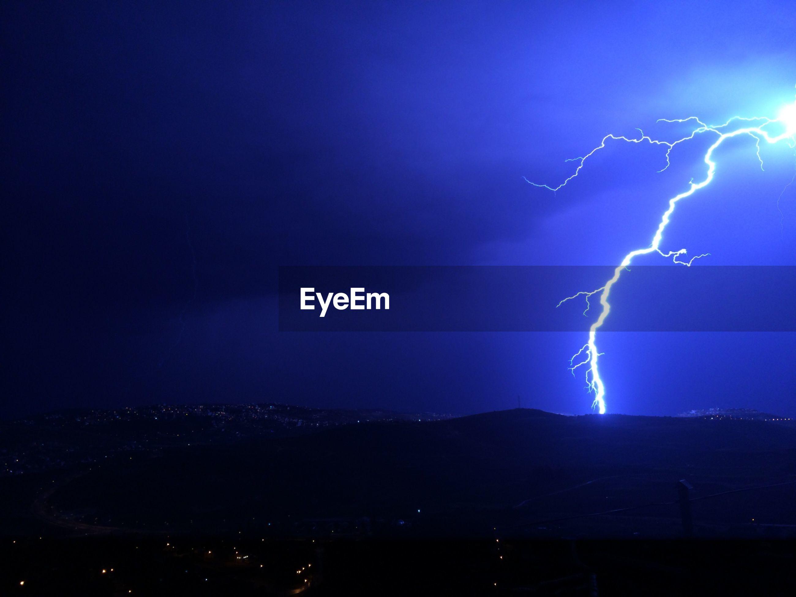 Lightning strike against blue sky