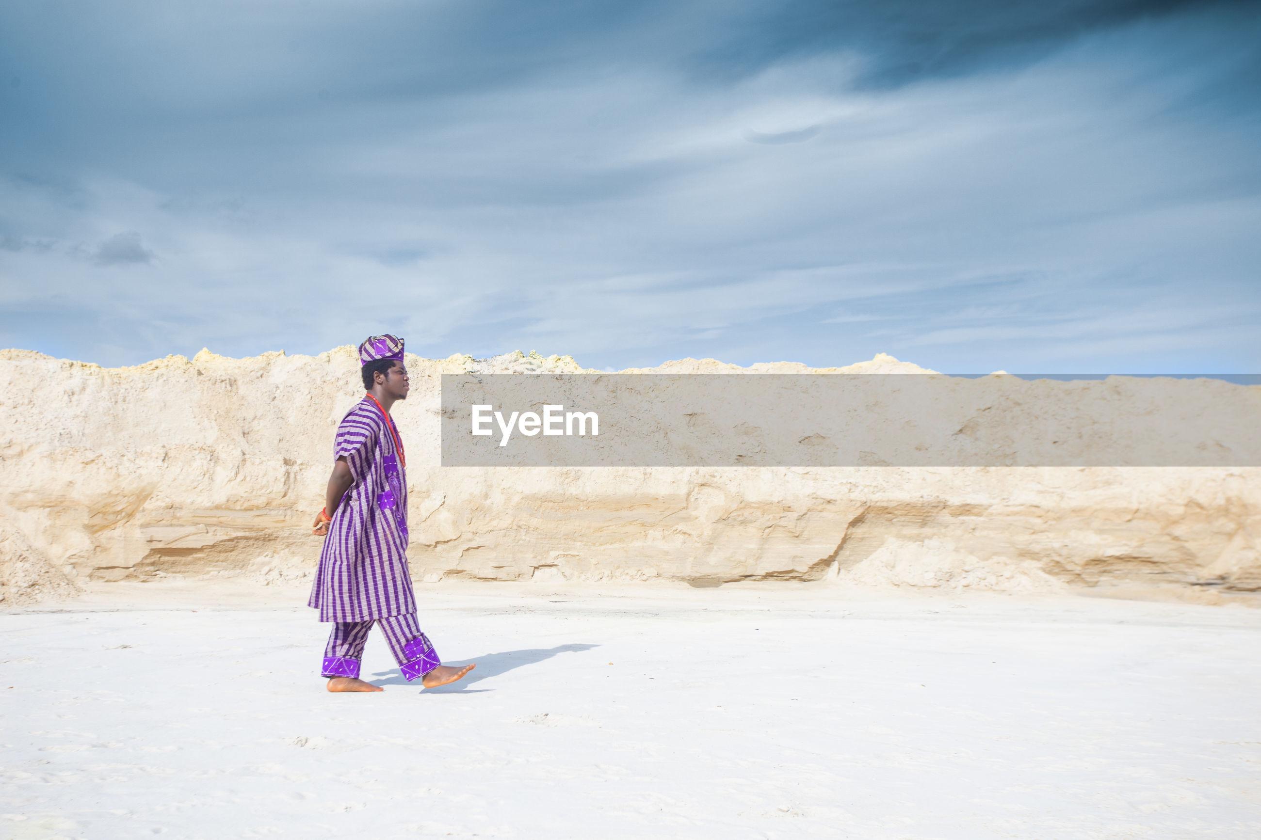 Man standing on beach against sky