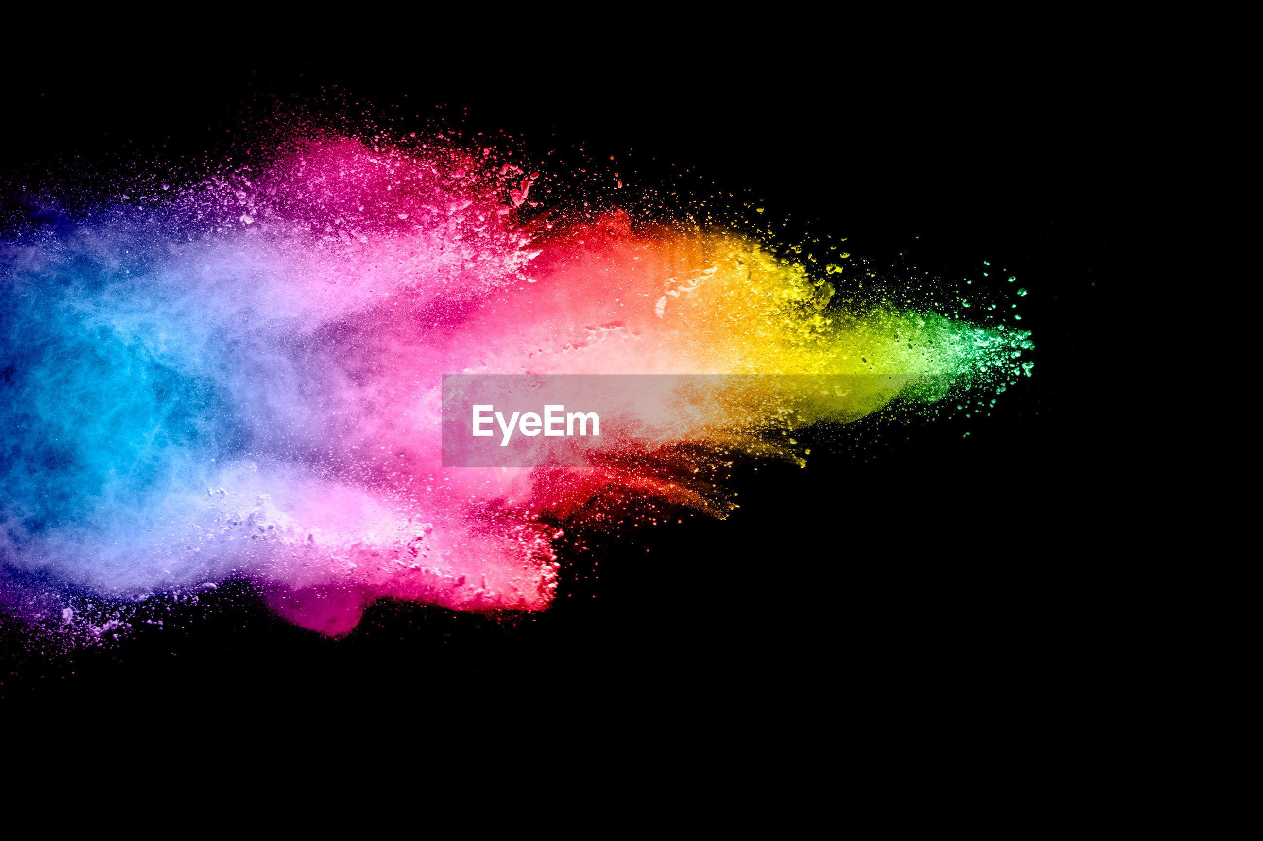 Colorful powder paint against black background