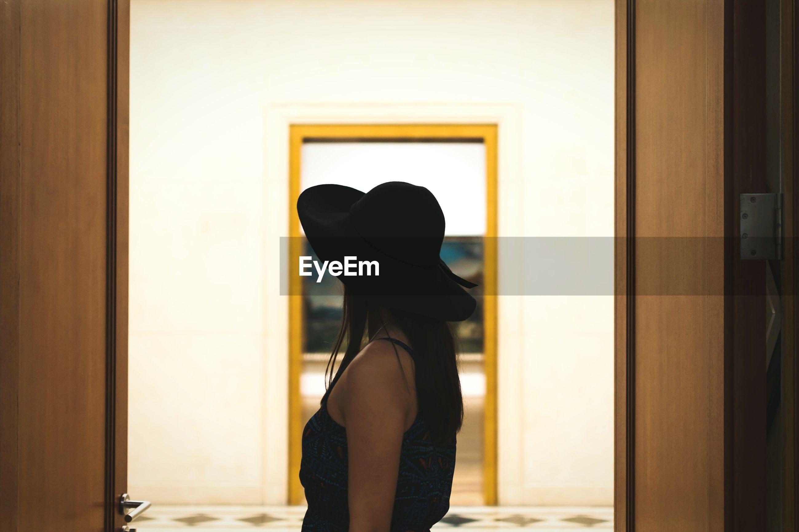 Side view of woman standing against doorway